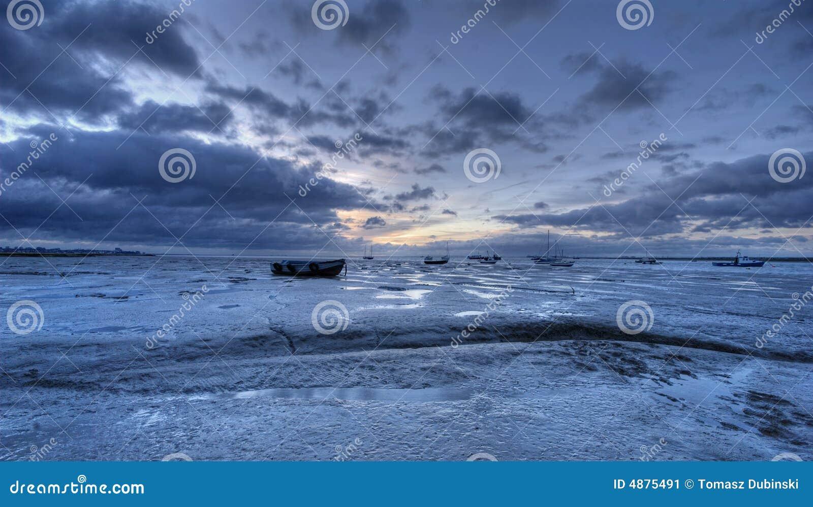 Salida del sol y playa fangosa