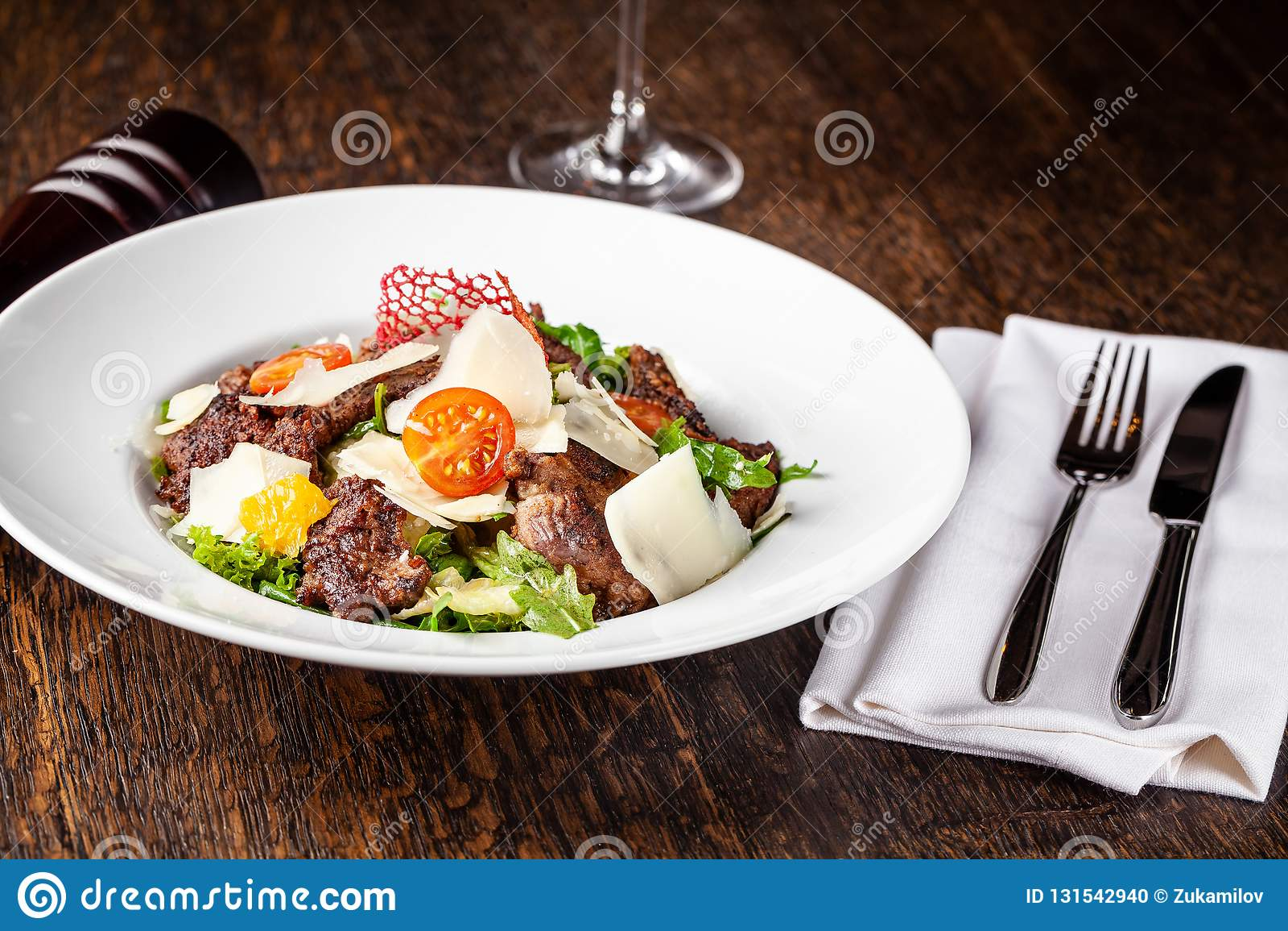 Sallad från blandningen av grönsallat, grönsallat och isberget lämnar, med körsbärsröda tomater, apelsinen och grillat nötkött på