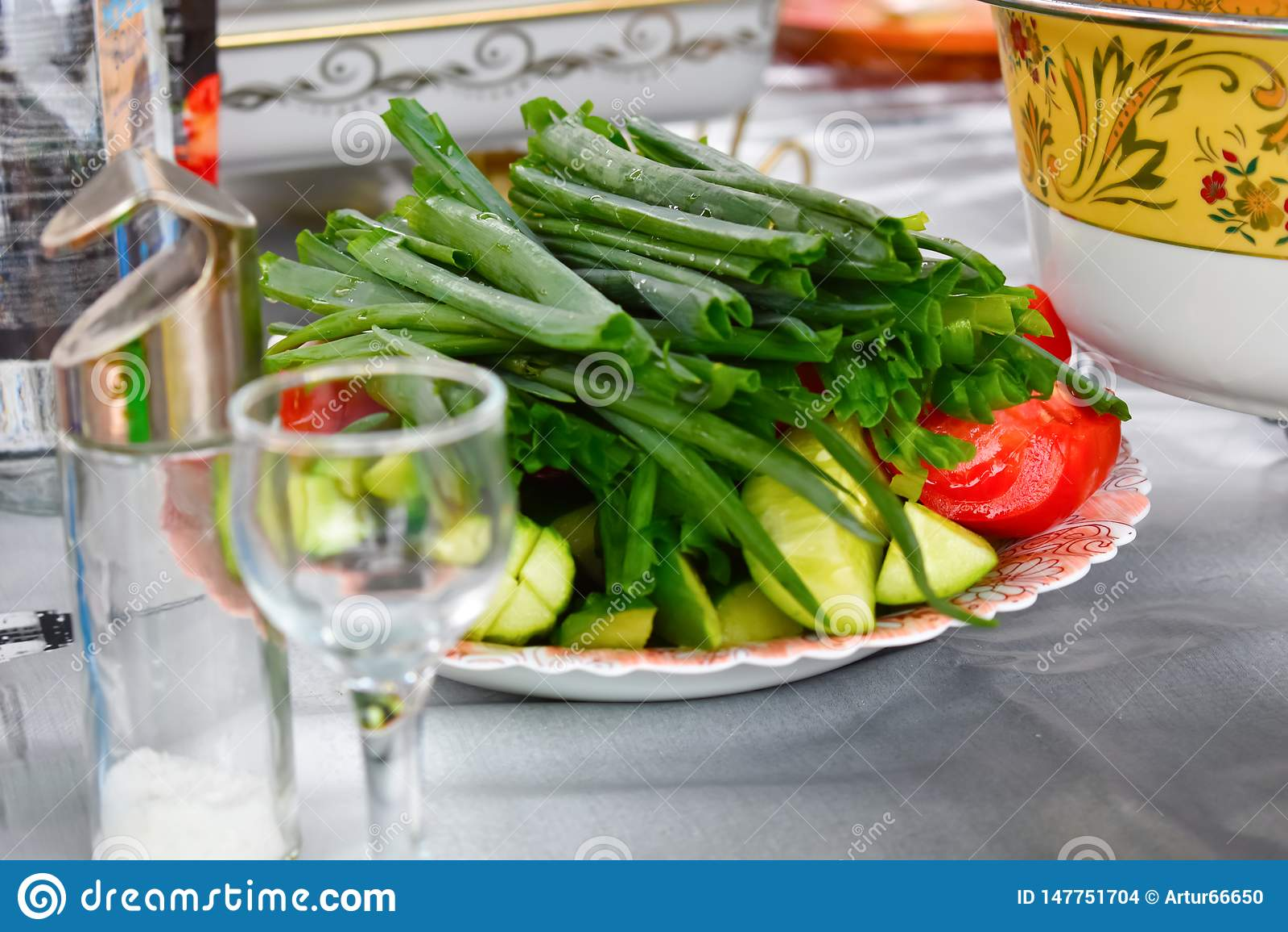 Salladslökar, gurkor och tomater på ett maträttslut upp