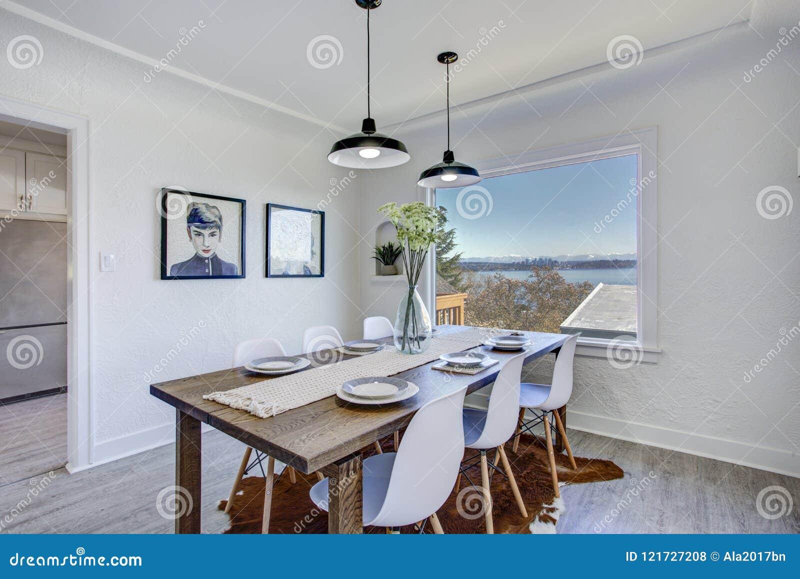 Salle à manger avec les murs blancs et la table en bois