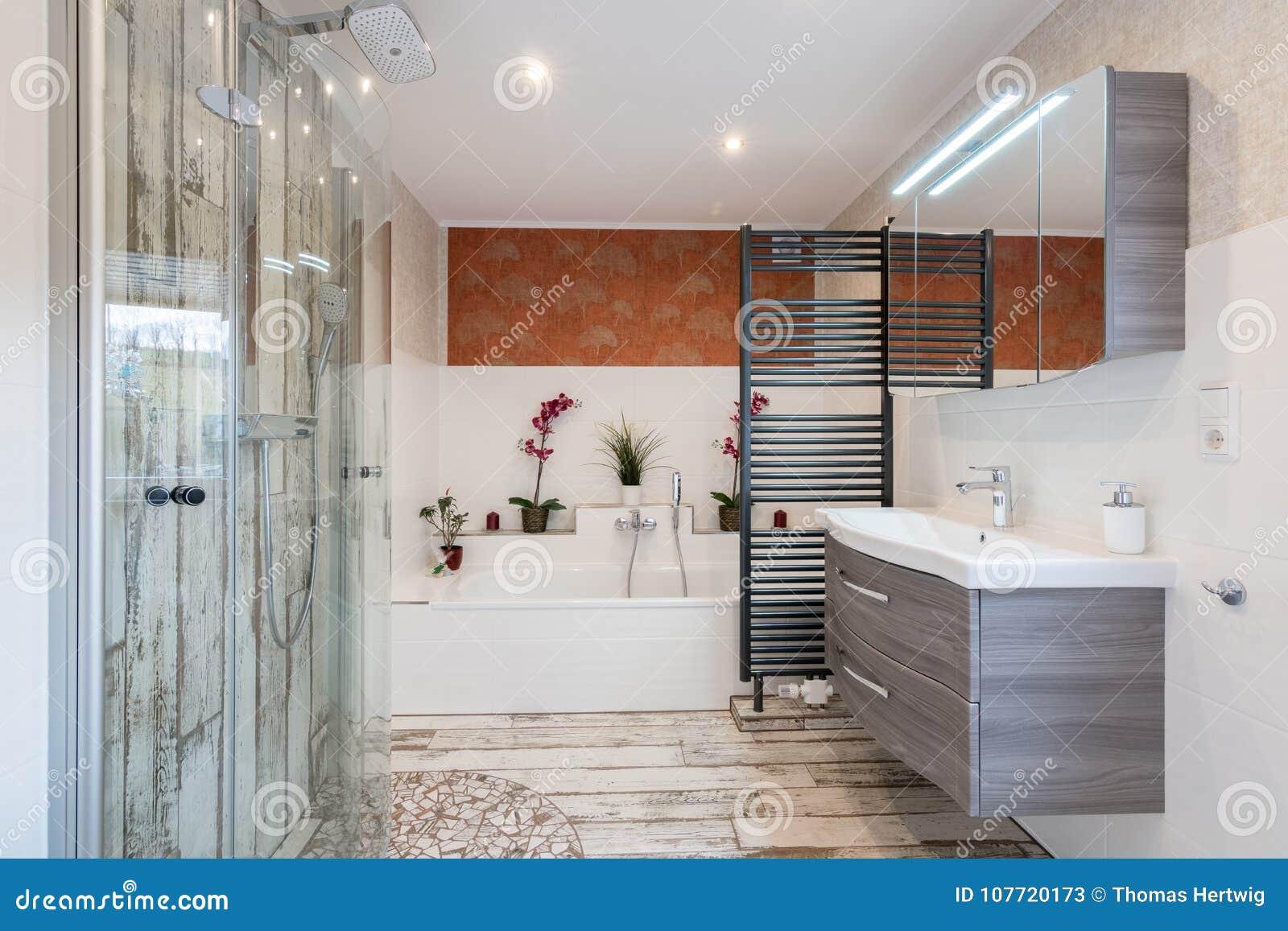 Salle de bains moderne dans le style de vintage avec l évier, la baignoire, la douche en verre et le dessiccateur noir de serviet