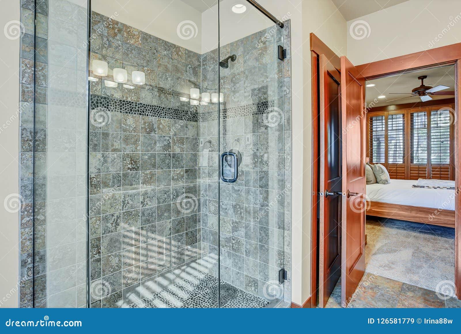 Salle de bains principale avec la promenade en verre dans la douche