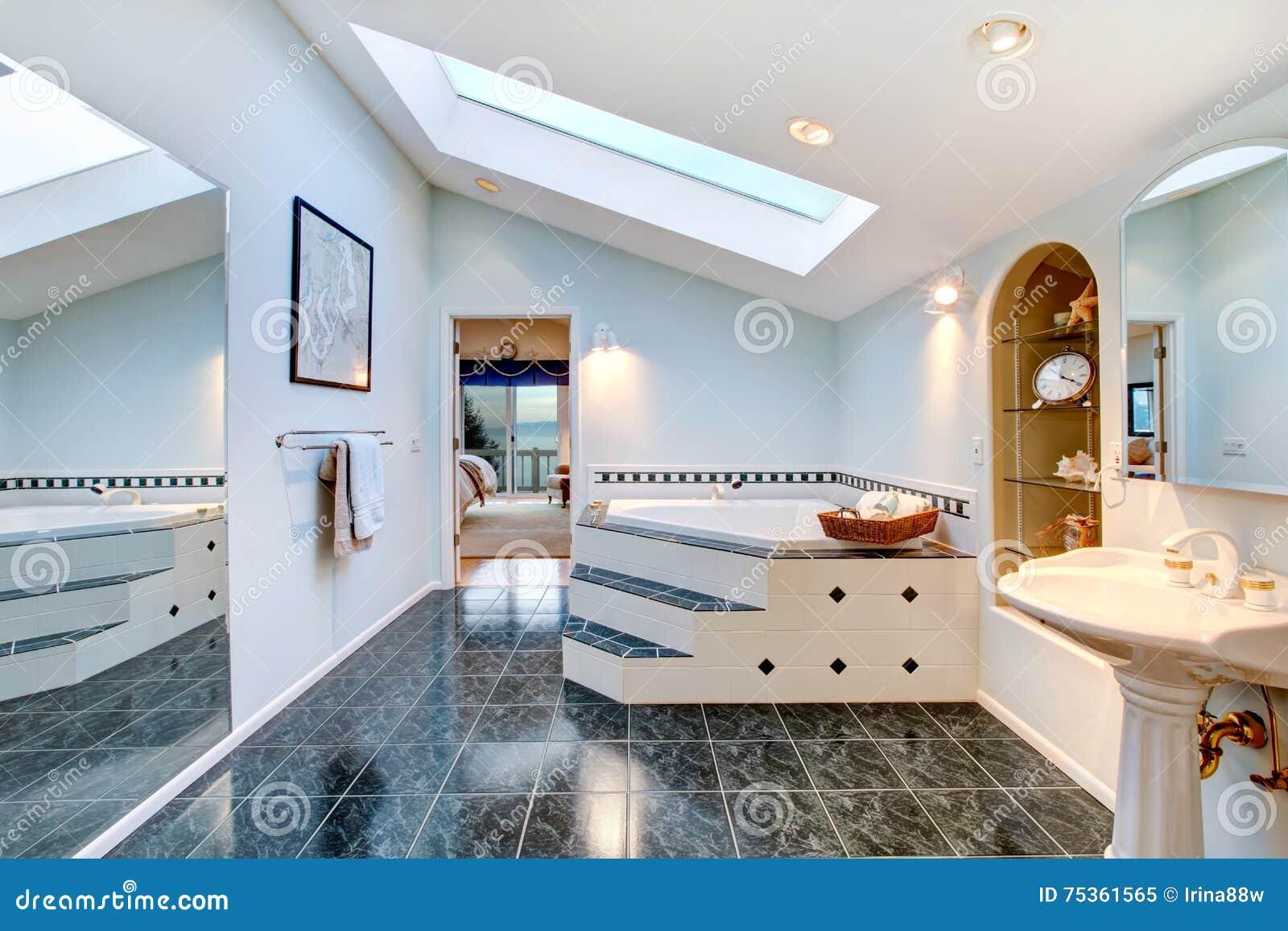 salle de bains principale avec le plancher de tuiles et la baignoire