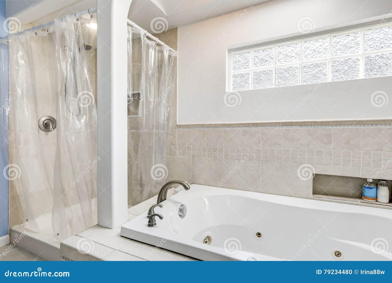 Salle de bains propre blanche avec l'équilibre beige de tuile et ...