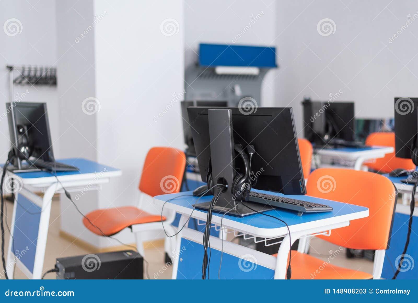 Salle de classe vide d ordinateur avec les bureaux bleus lumineux et les chaises oranges enfants de enseignement programmation