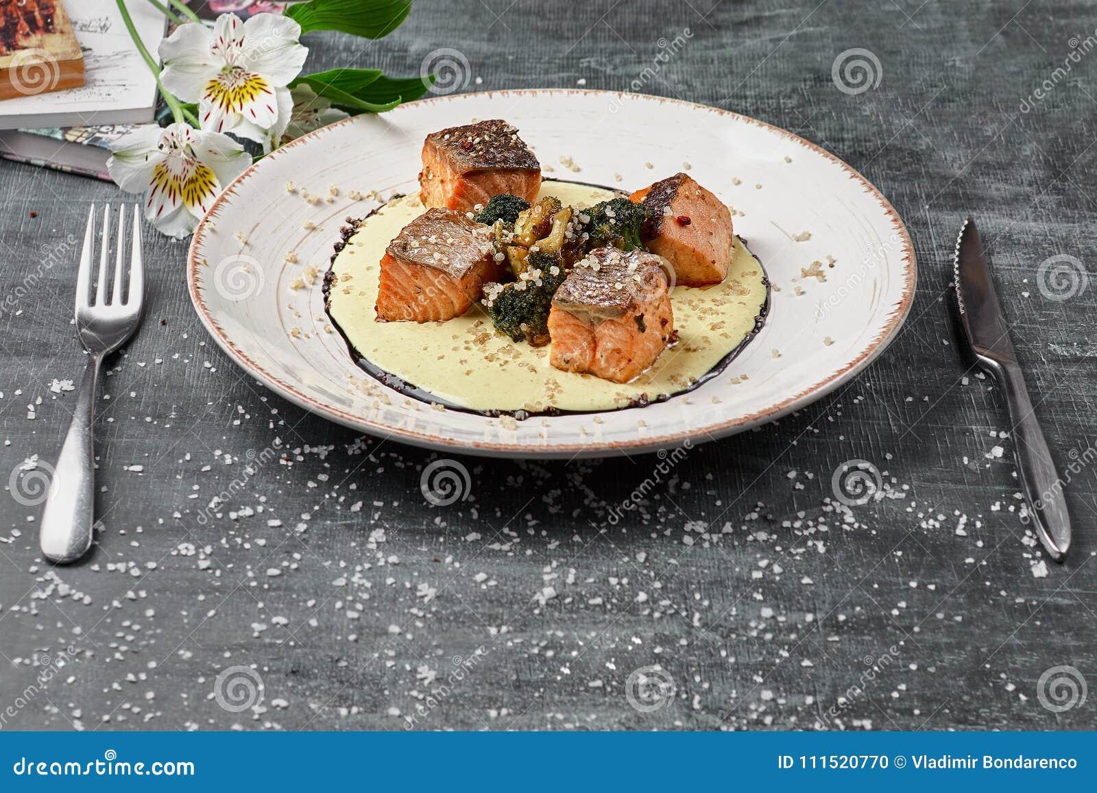 Salmões cozidos dos peixes no molho do açafrão com brócolis Menu dietético Menu dos peixes Marisco - salmão