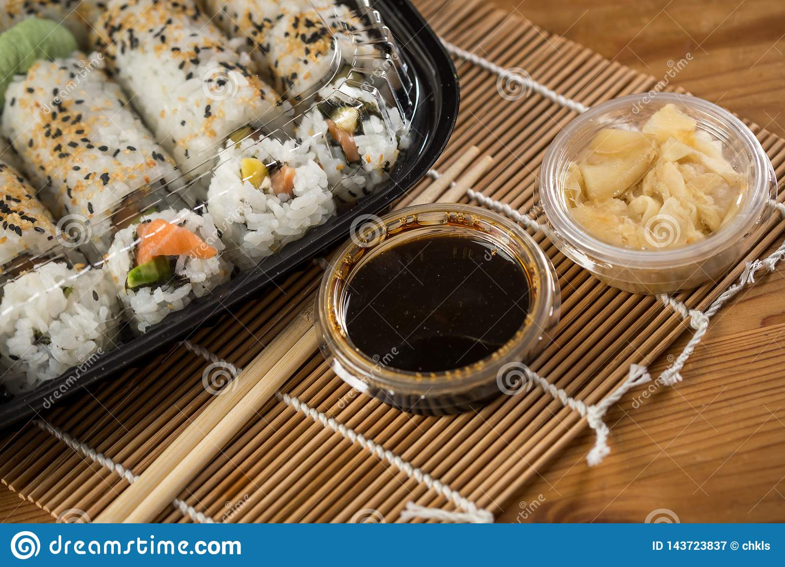 Salmon, avocado and mango inside out California sushi with soy sauce, pickled ginger, soy sauce and wooden chopsticks in plastic
