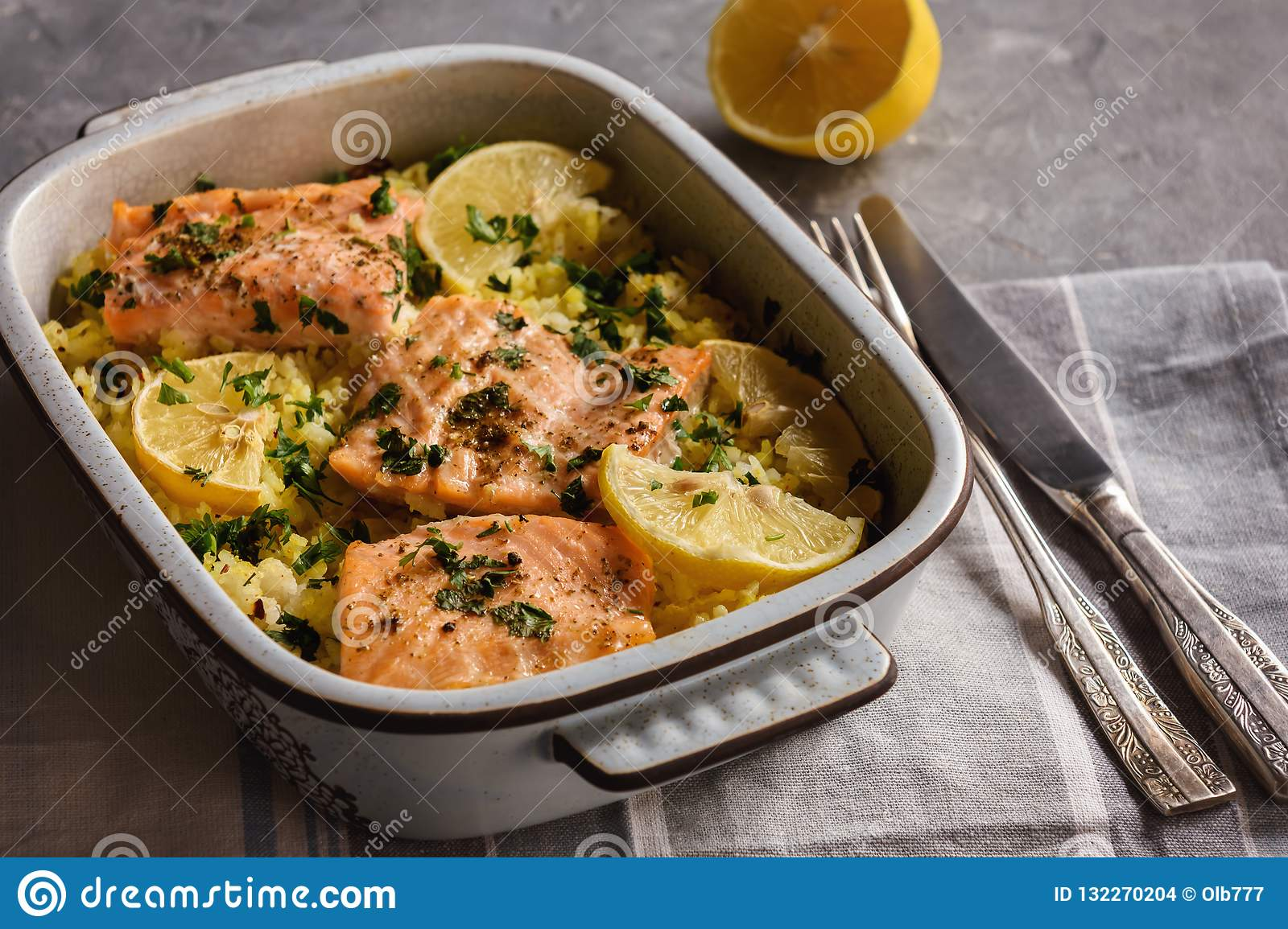 Salmon baked on oven with rice and lemon.