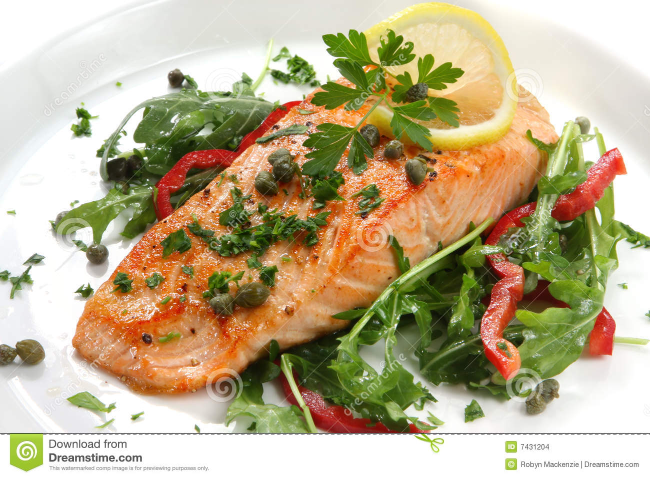 Atlantic salmon with a rocket salad, garnished with lemon, capers and ...