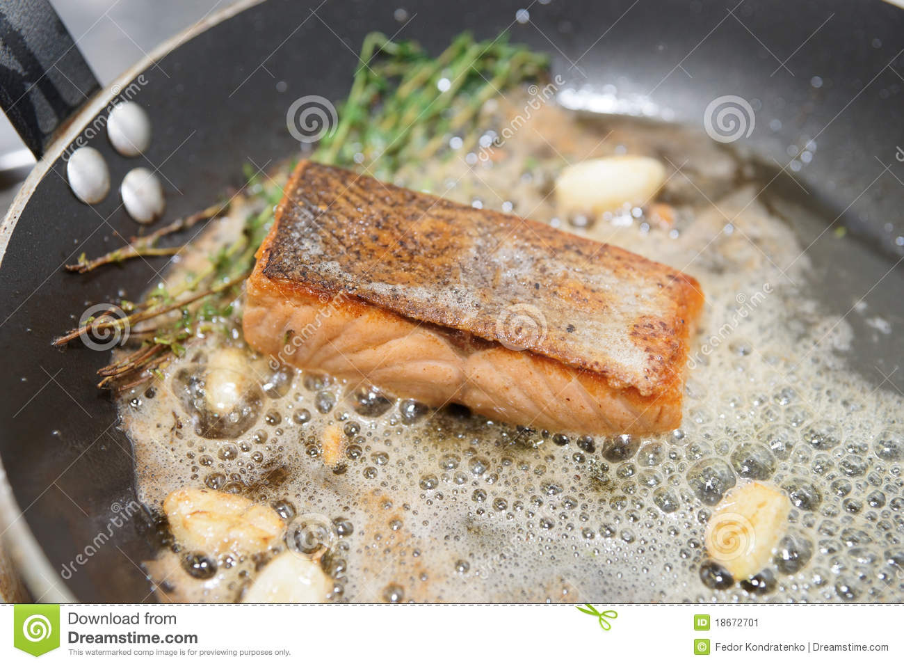 Salmon fillet being fried with thyme and garlic in butter.