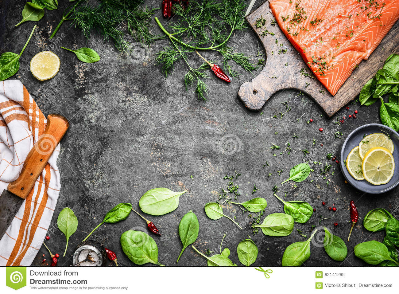 Salmon fish fillets on cutting board and fresh ingredients for cooking on rustic background, top view