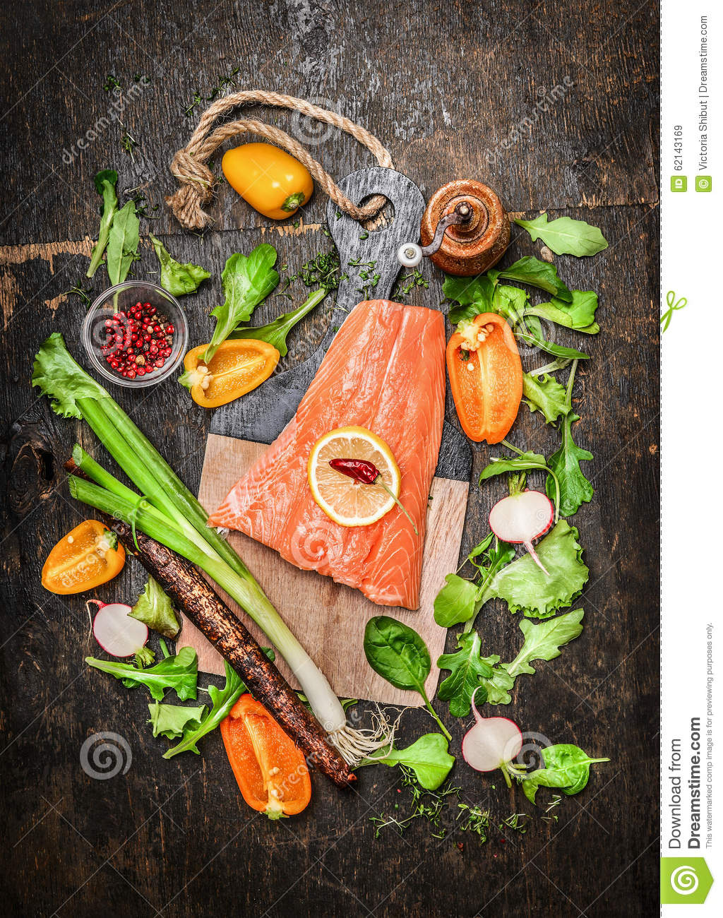 Salmon fish fillets on cutting board with fresh vegetables for Fish fillet board