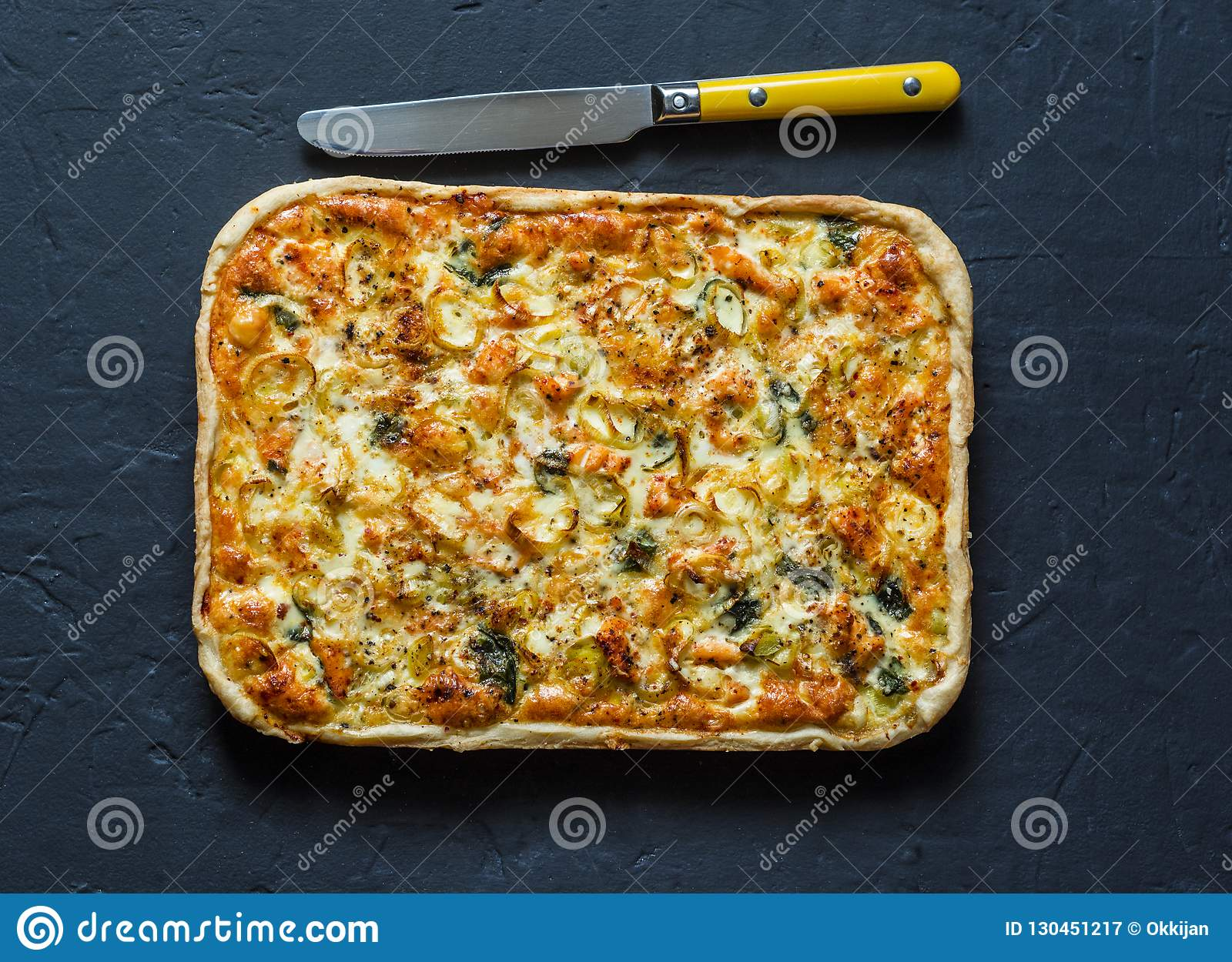 Salmon, leek, spinach, cheese puff pastry pie on dark background