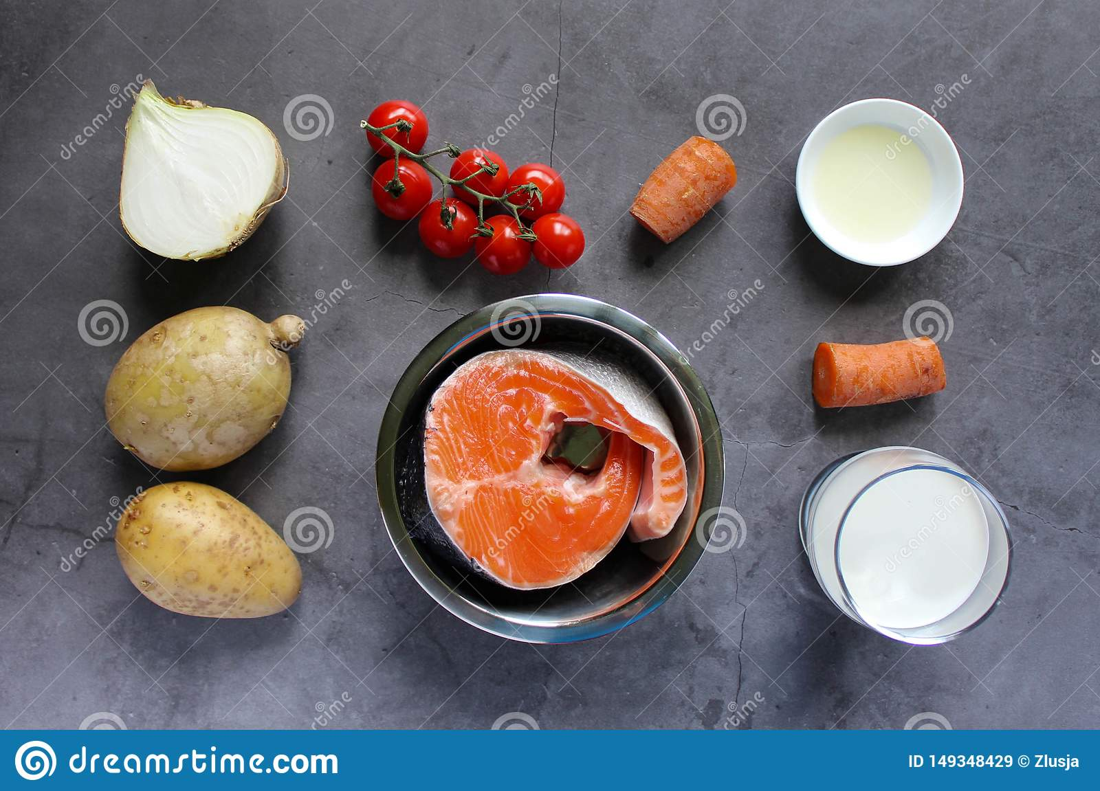 Ingredients for fish soup: salmon, onion, carrot, potato, cherry tomatoes, cream, olive oil