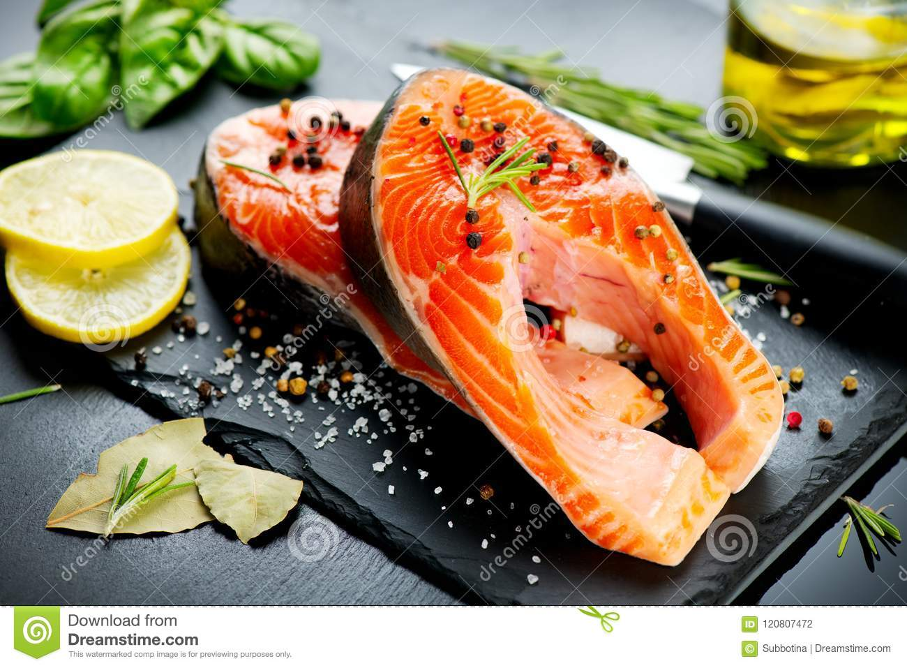 Salmon Raw Trout Fish Steak With Herbs And Lemon On Black Slate