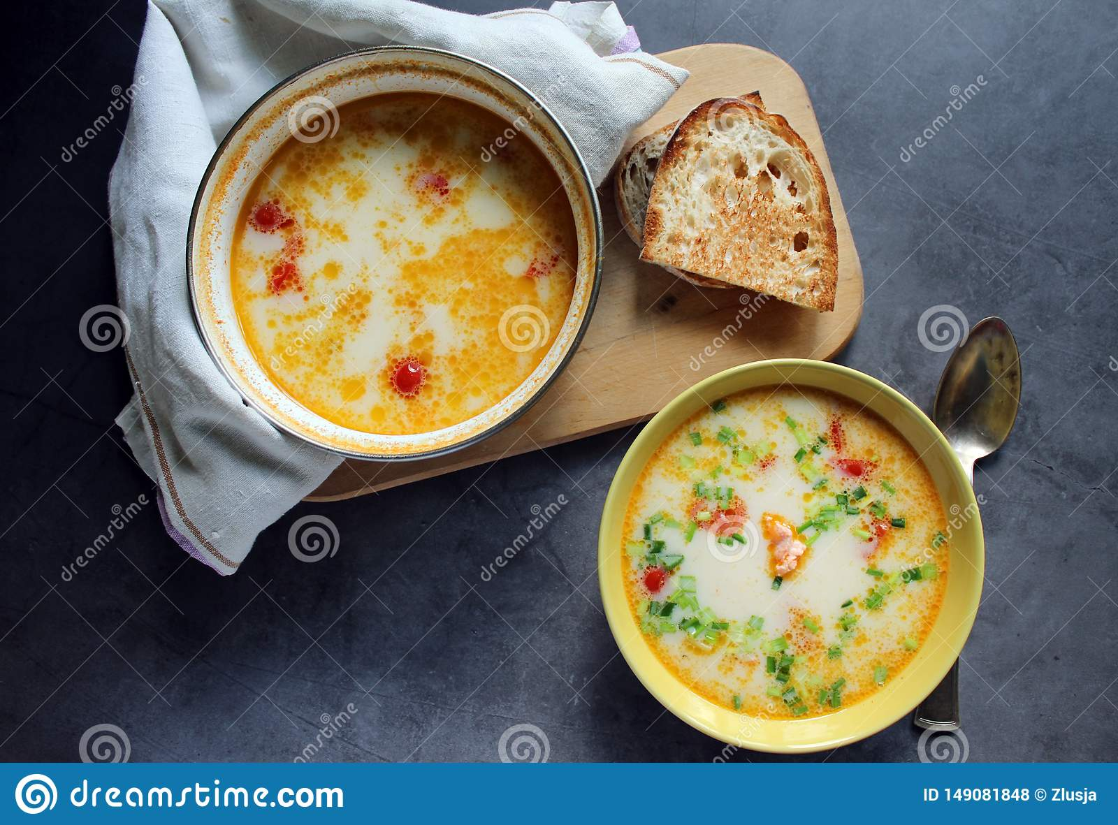 Salmon soup with cream and vegetables in a yellow plate. saucepan with salmon soup in a towel. bread on the board. on a dark backg