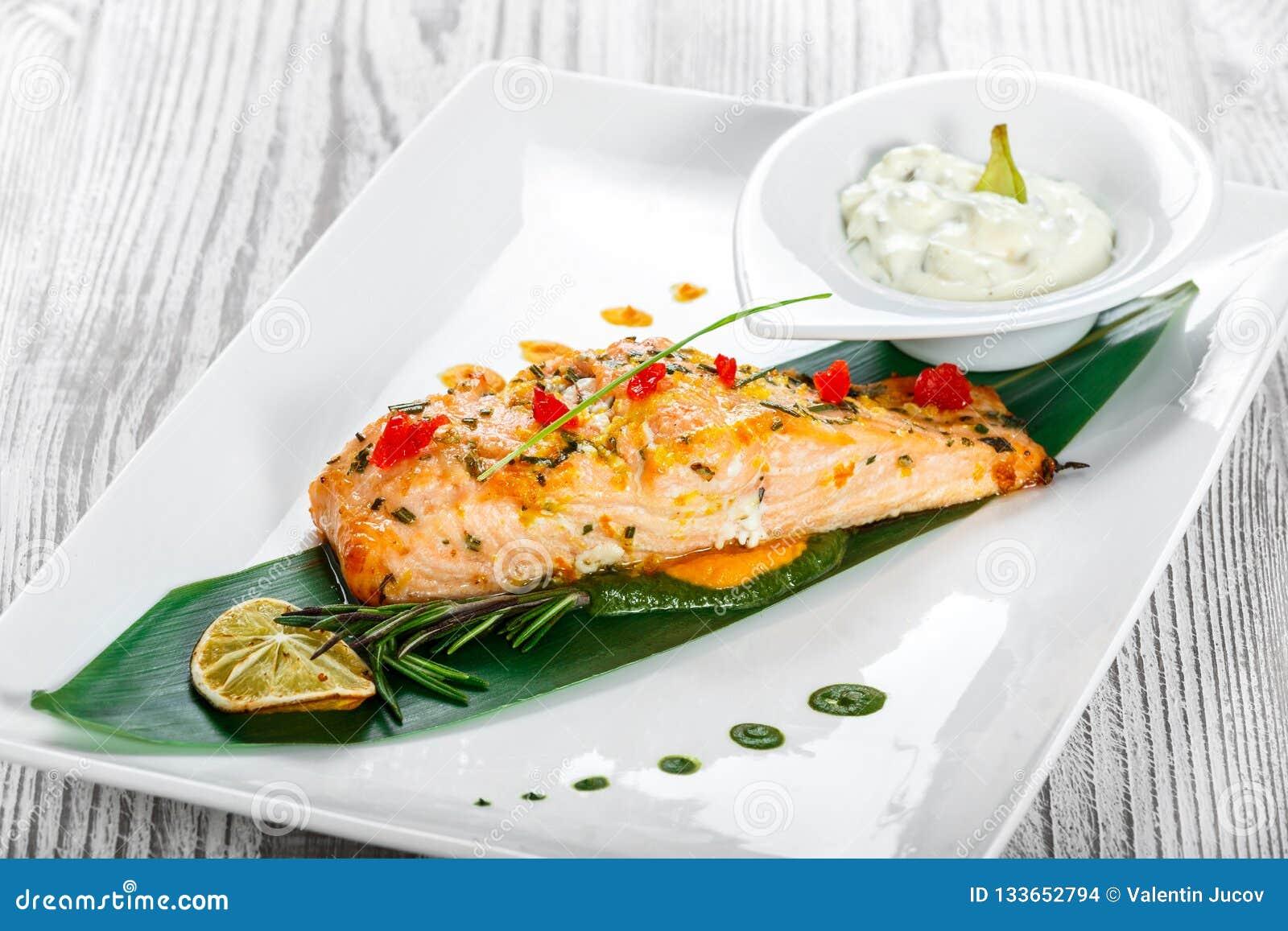 Salmone al forno con la salsa, i rosmarini ed il limone di formaggio su fondo di legno Piatto di pesci caldo