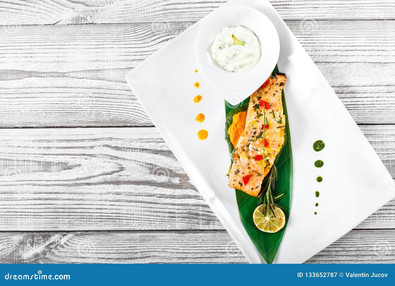 Salmones cocidos con la salsa, el romero y el limón de queso en fondo de madera Plato de pescados caliente