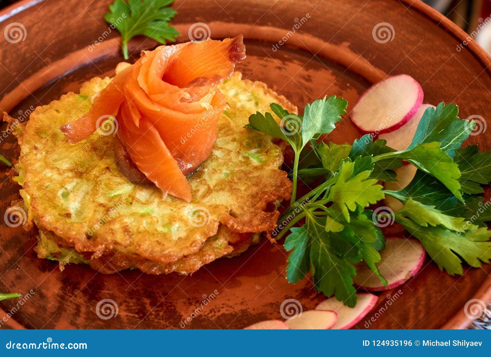 Salmones frescos encima de las crepes del calabacín con perejil y el rábano