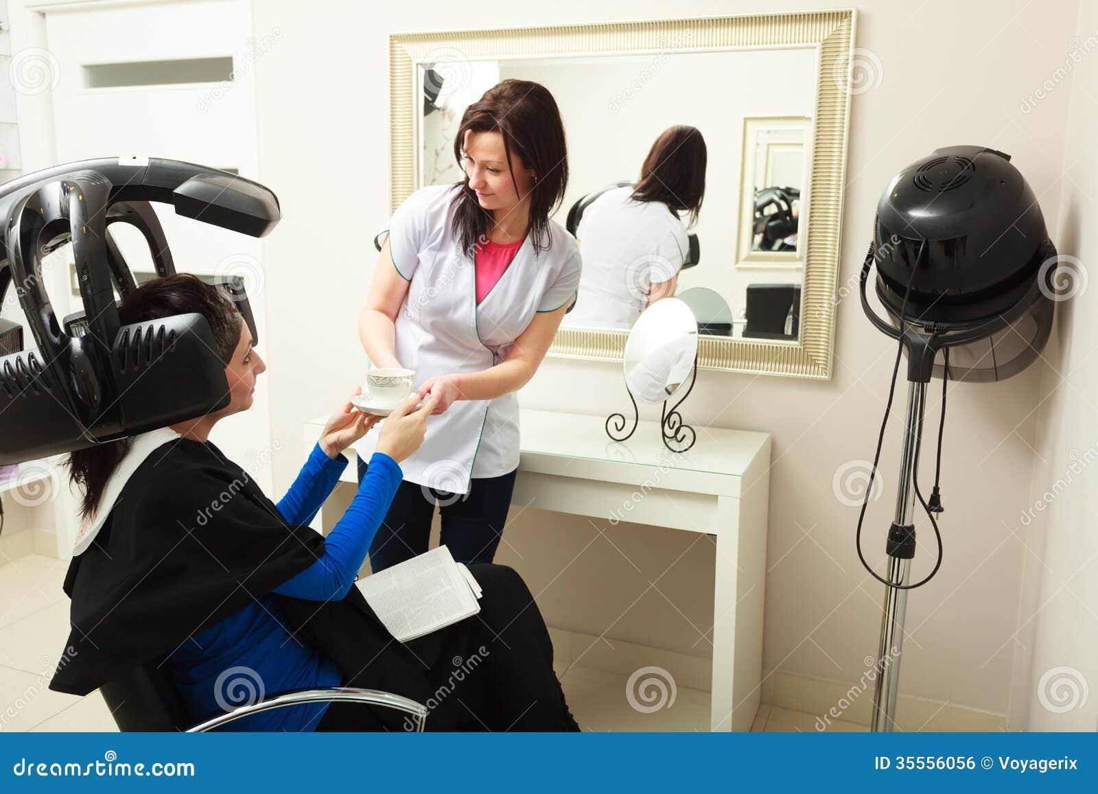salon de coiffure coiffeur donnant la cliente de femme de caf de tasse quipement moderne. Black Bedroom Furniture Sets. Home Design Ideas