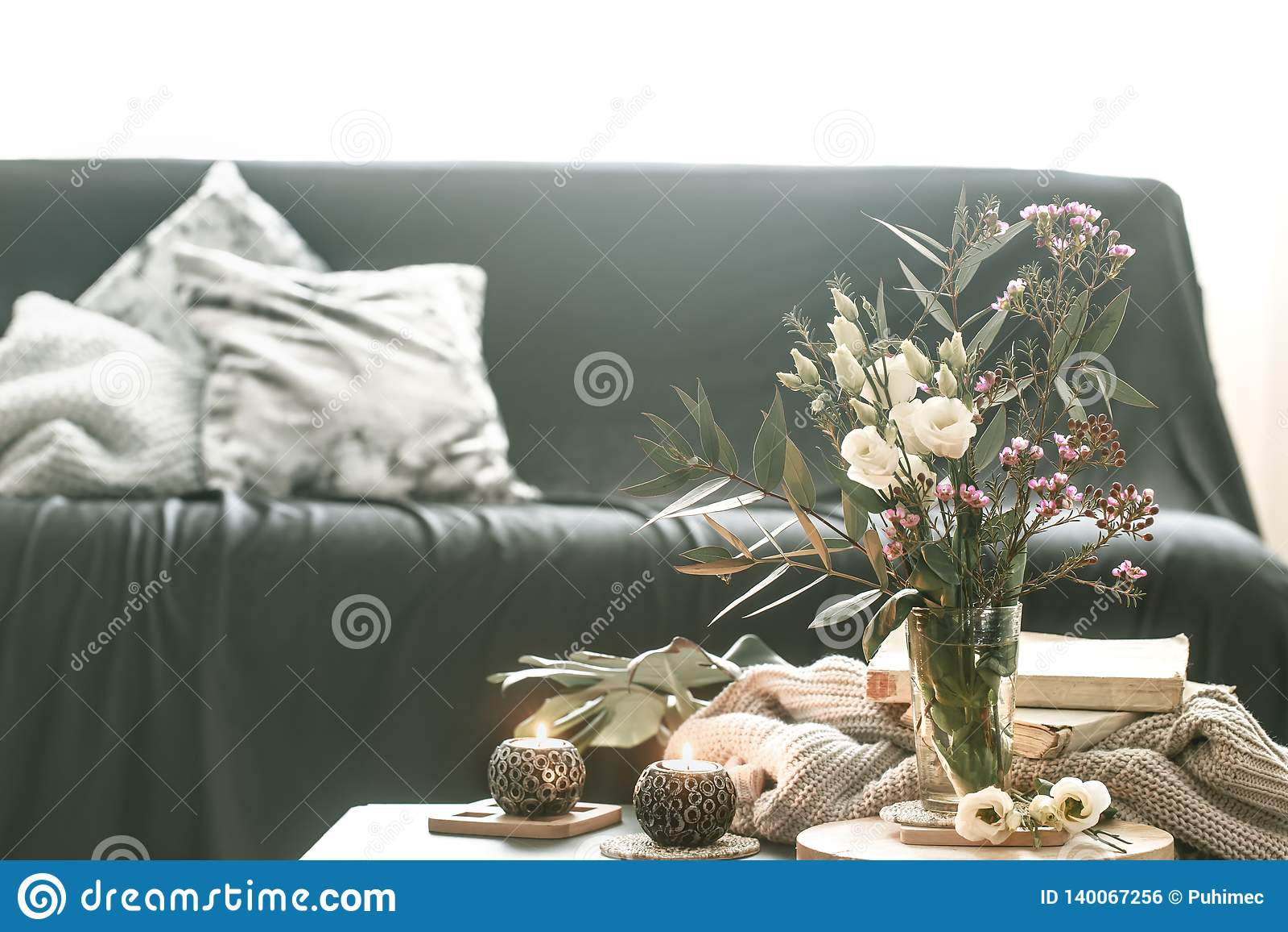 Salon intérieur à la maison confortable avec un vase de fleurs et de bougies