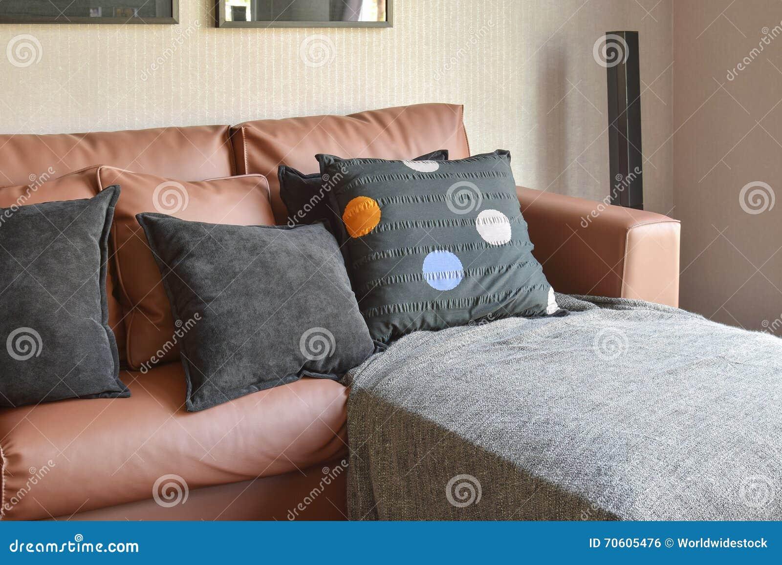 Salon moderne avec le sofa en cuir brun et les oreillers noirs ...