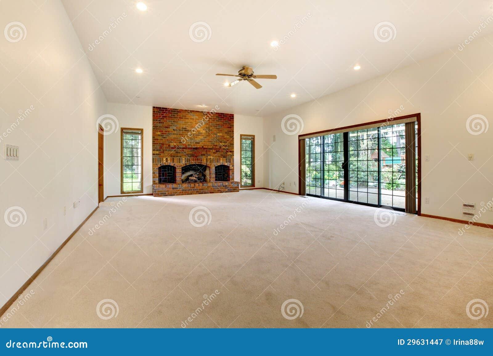 Salon vide très grand avec la cheminée de brique.