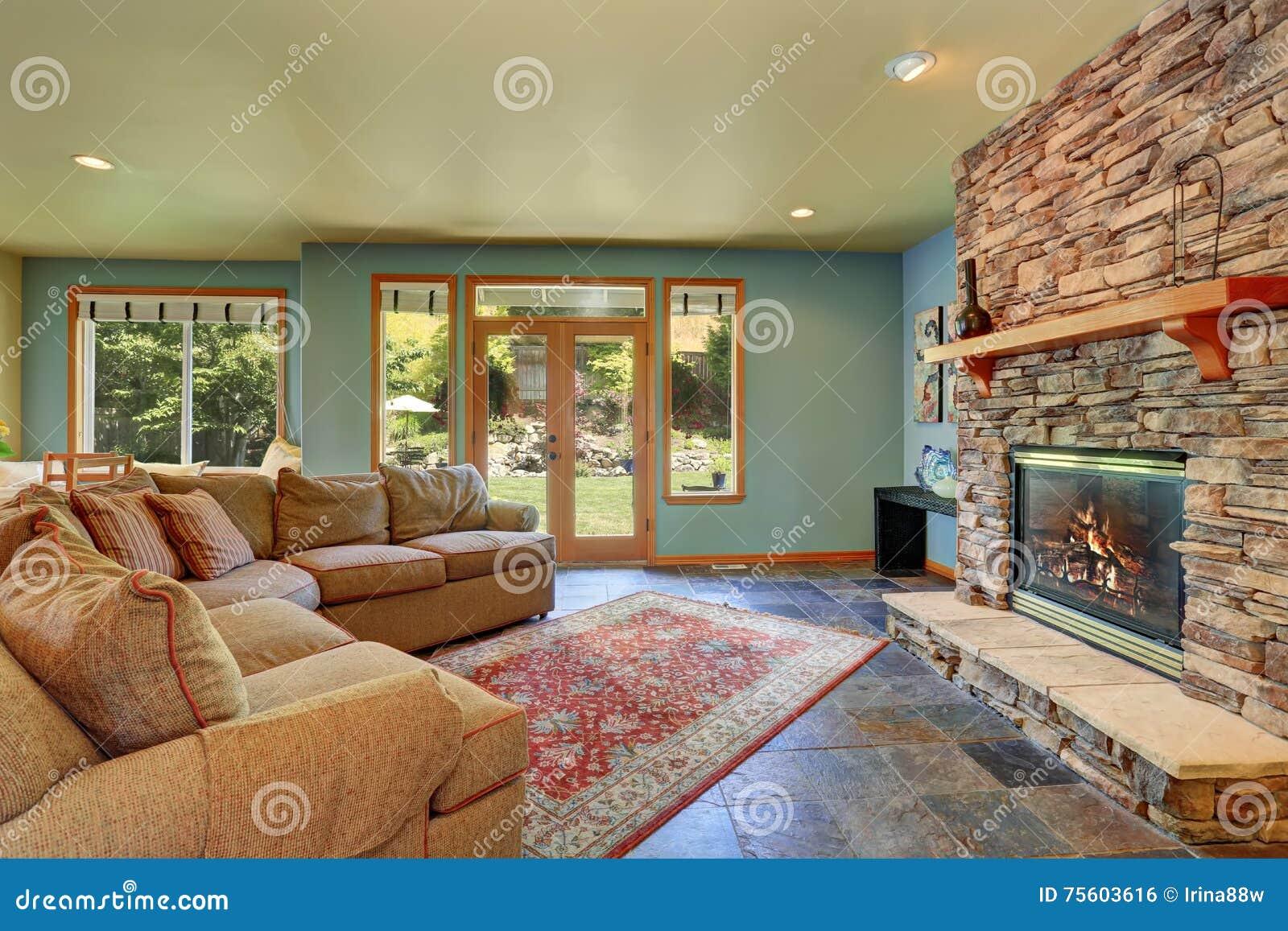 Salone accogliente con le pareti blu ed il camino di pietra delle
