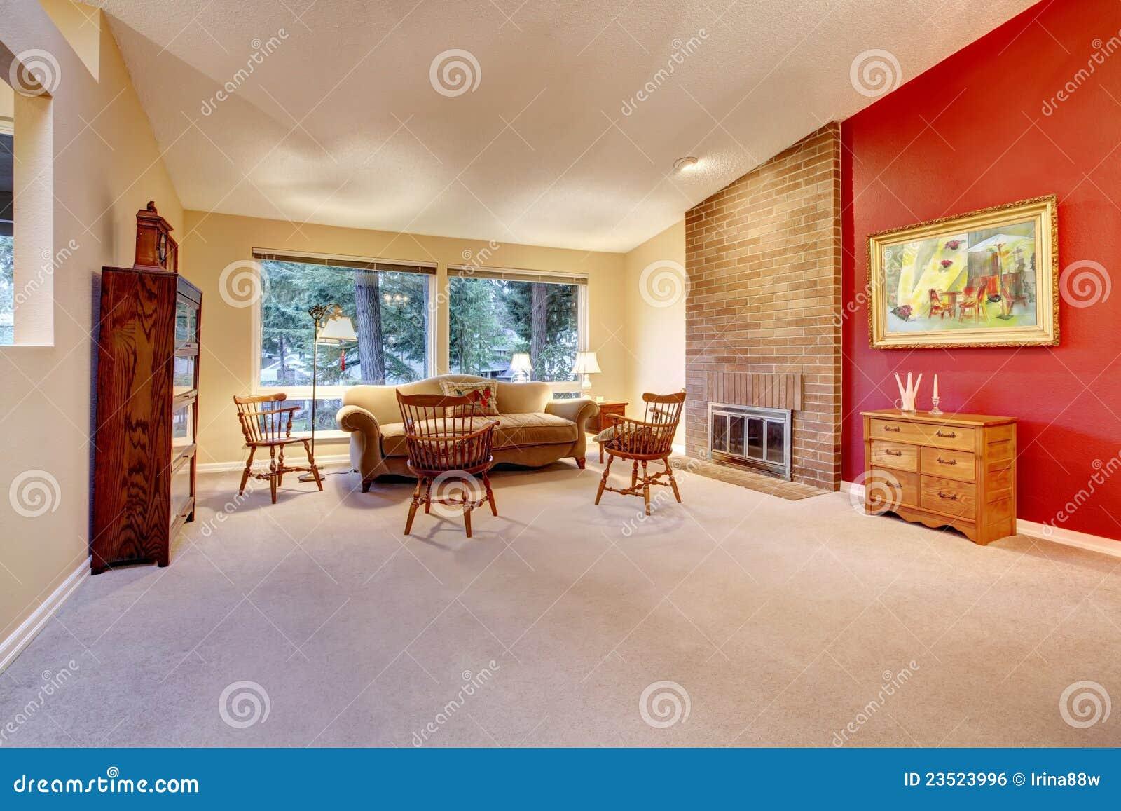 Salone vuoto con il camino del mattone ed il pavimento di tappeto ...