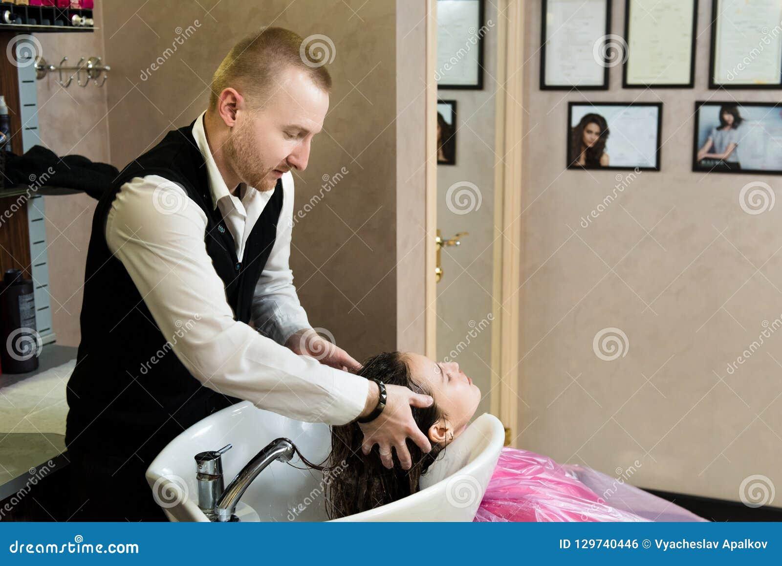 Salone di bellezza, cura di capelli e concetto della gente - le mani del parrucchiere che lavano la giovane donna felice si dirig