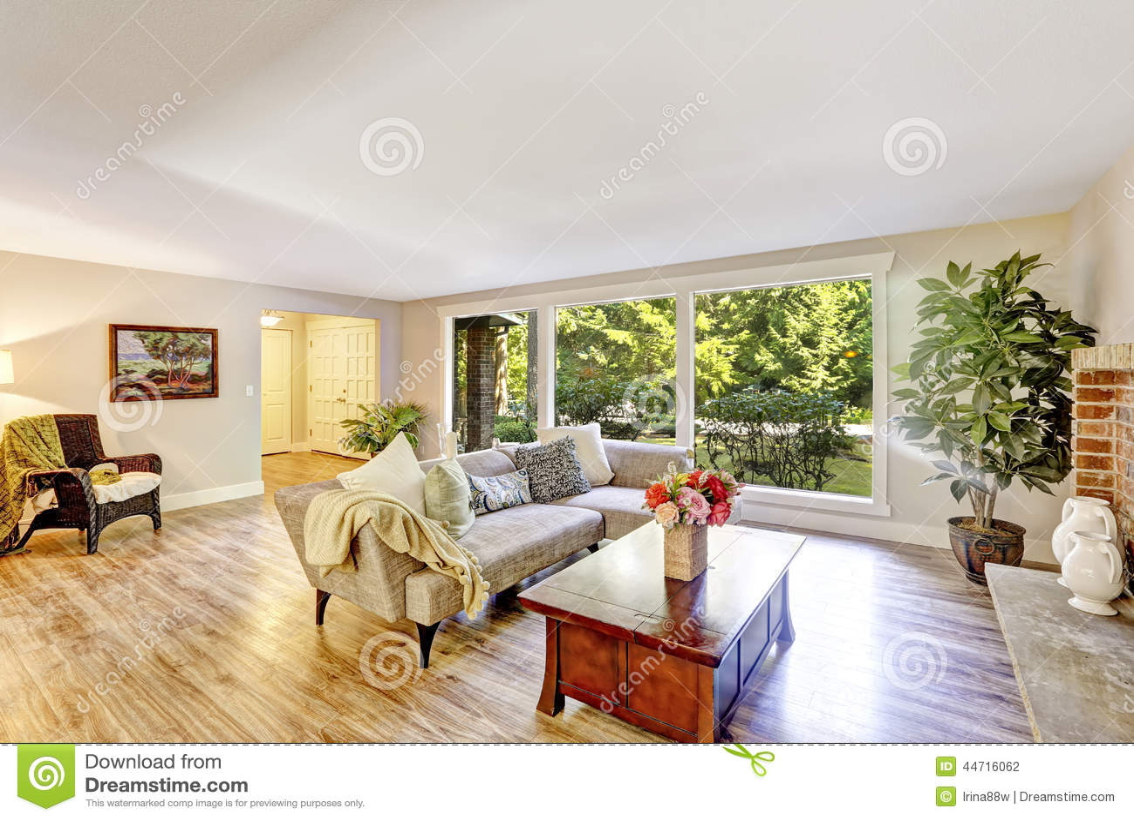 Salone luminoso spazioso con la parete di vetro decorata for Parete sala