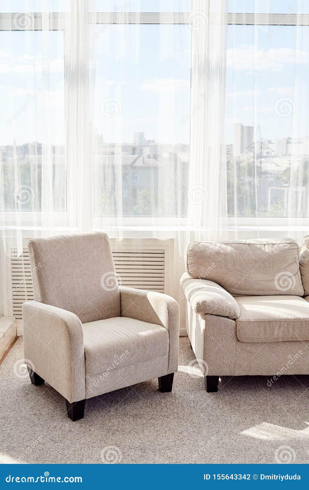 Salone moderno alla moda con il sofà e poltrona beige comoda e grande finestra, spazio della copia Interiore del salone