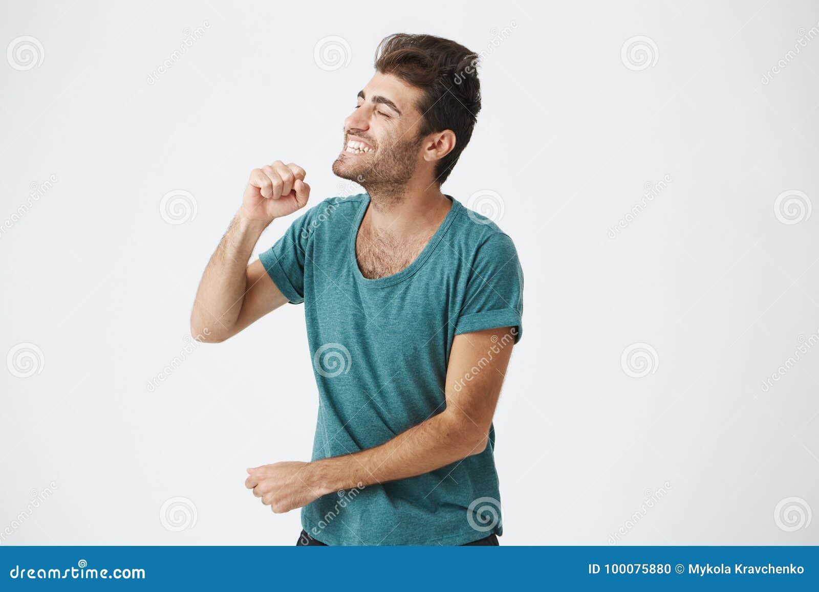 Salowy portret ekspresyjny hiszpański dojrzały facet śpiewa z eleganckim ostrzyżeniem w błękitnej koszulce, jaskrawy ono uśmiecha