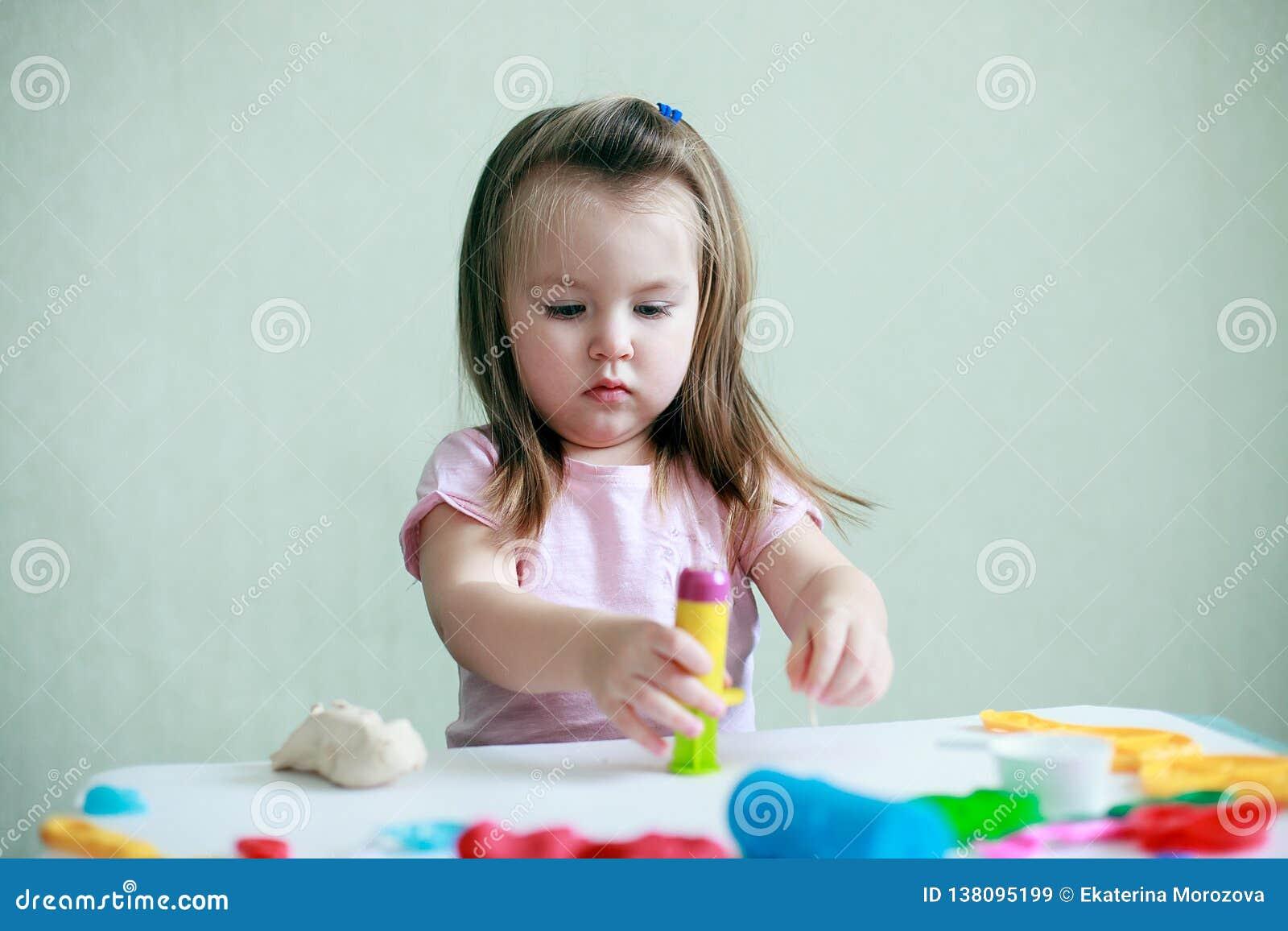 Salowy portret potomstwa 2 roku szczęśliwej uśmiechniętej caucasian dziecko dziewczyny bawić się z sztuki ciastem