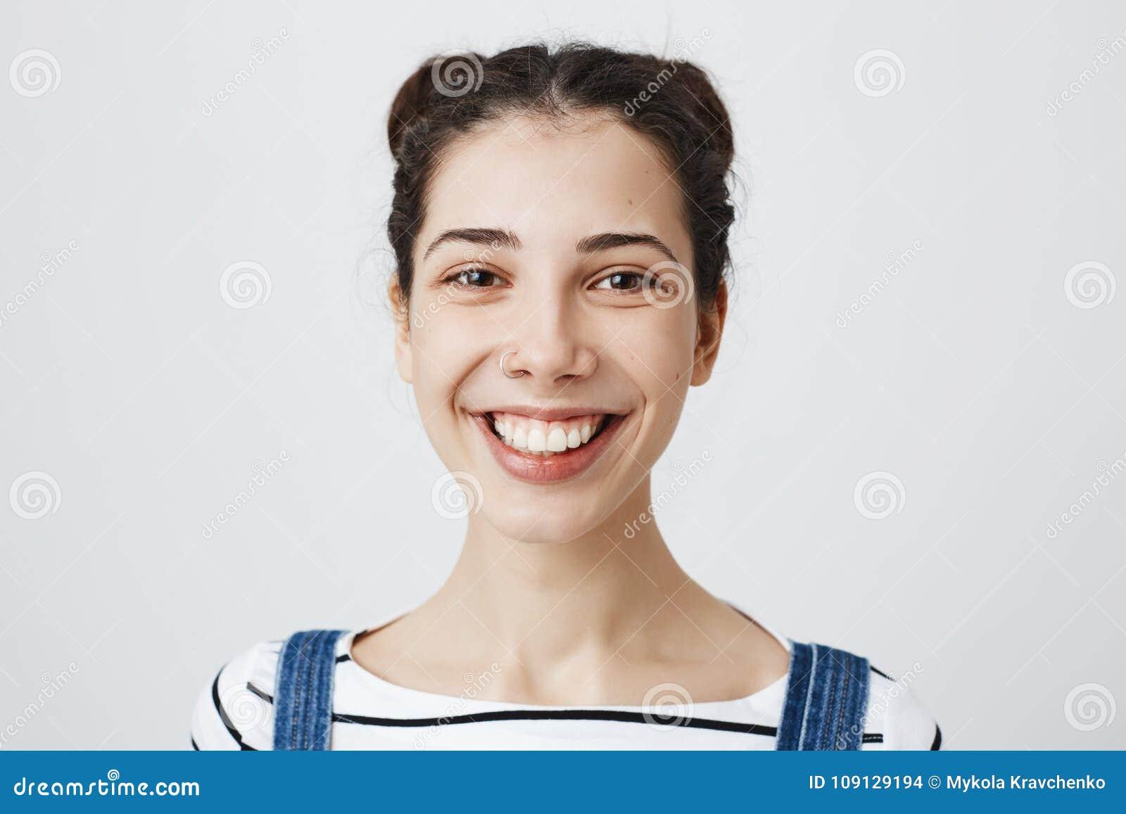 Salowy strzał śliczna młoda dorosła kobieta ono uśmiecha się szeroko z przebijającym nosem i modnym ostrzyżeniem, wyraża pozytywn