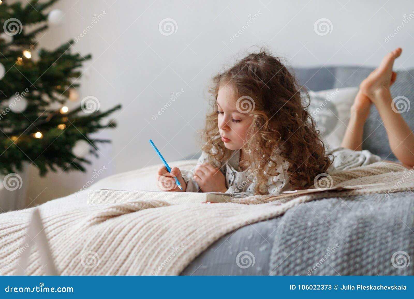 Salowy strzał baczna dosyć mała dziewczyna pisze liście Święty Mikołaj przed bożymi narodzeniami, myśleć jaki teraźniejszość ona