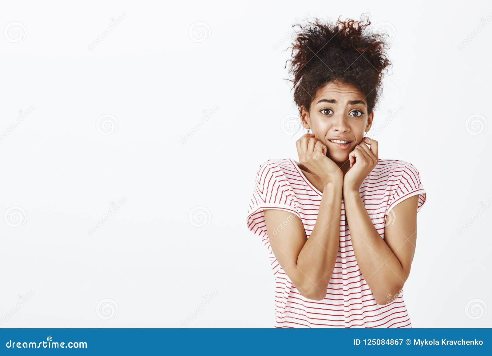 Salowy strzał bojaźliwa niepewna atrakcyjna garbnikująca kobieta z kędzierzawym włosy, dotyka twarz, podnośne brwi i uczucie,