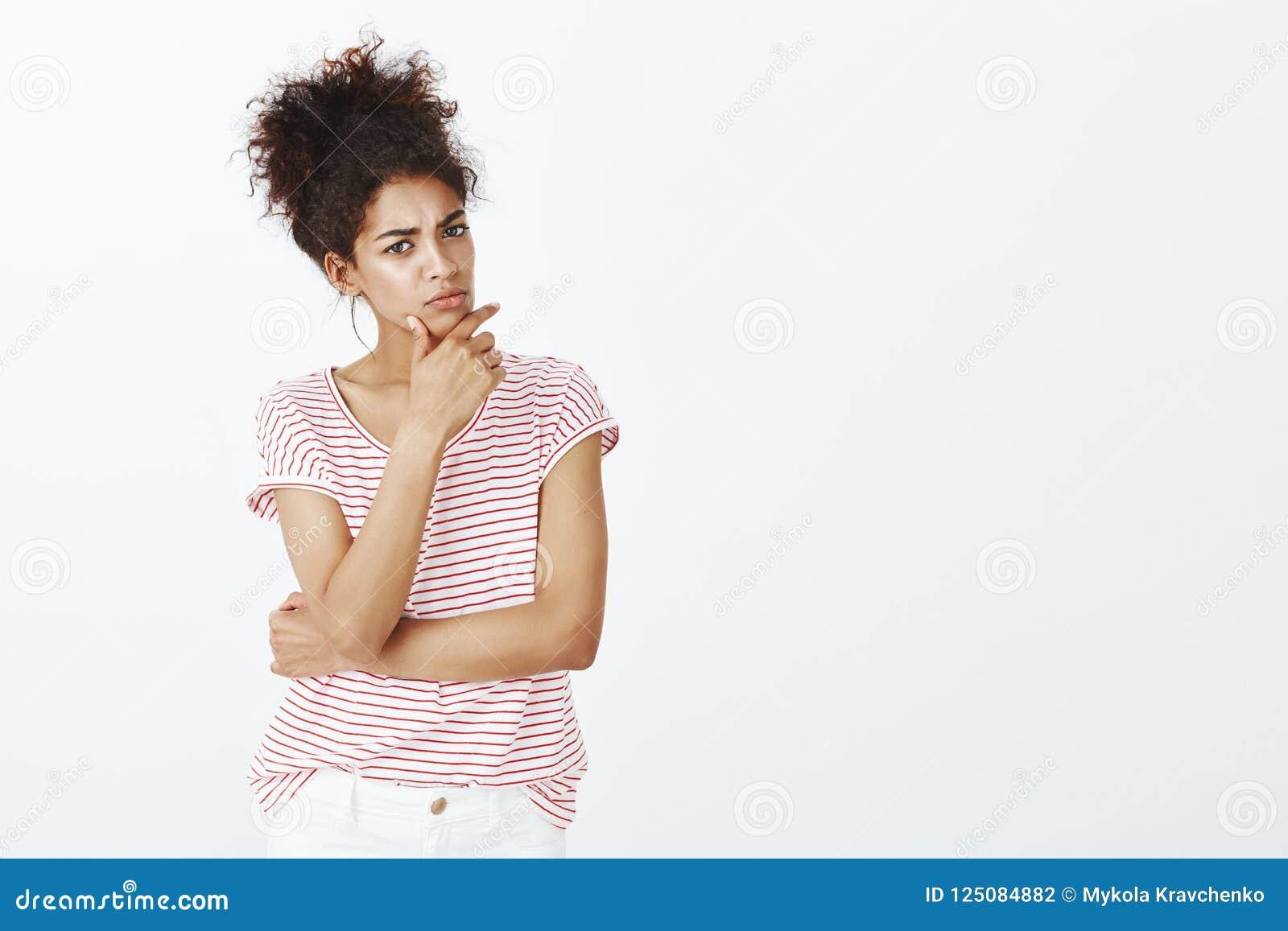 Salowy strzał intensywna mądrze śliczna kobieta z ciemną skórą i rozczesanym włosy, trzymający rękę na szczęce, marszczący brwi n