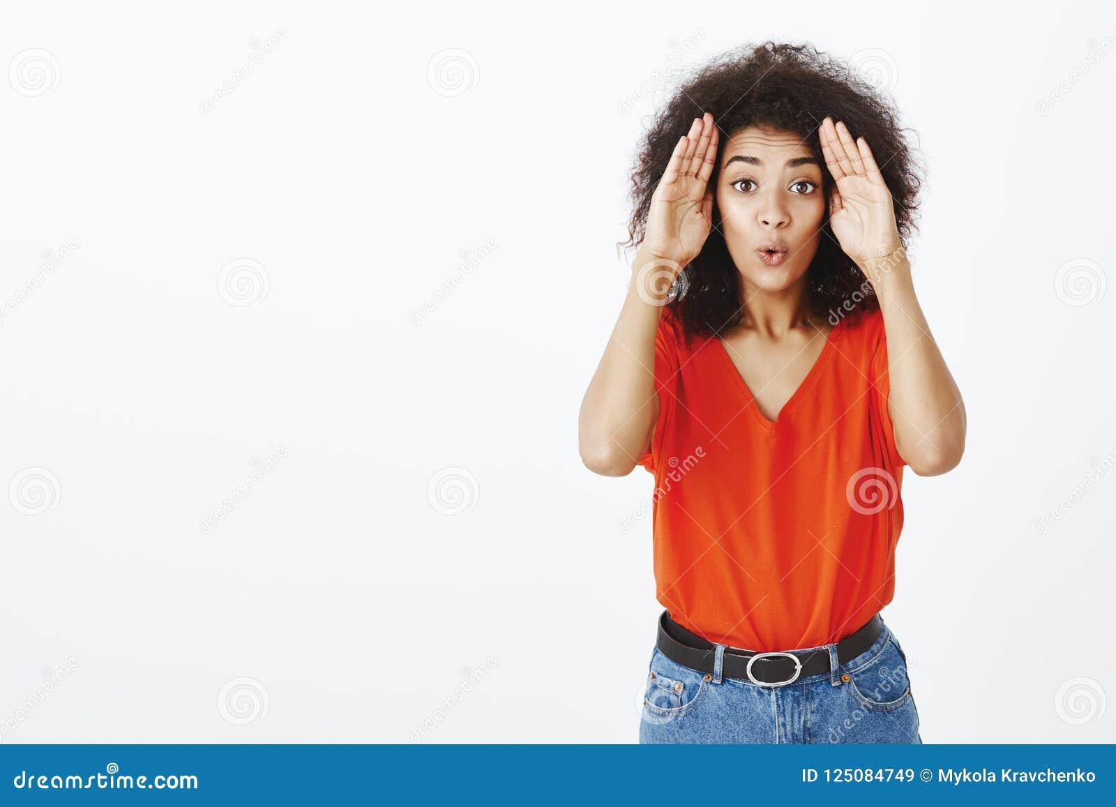 Salowy strzał miła atrakcyjna afrykańska kobieta z kędzierzawym ostrzyżeniem, trzymający palmy blisko, składający wargę i ono wpa