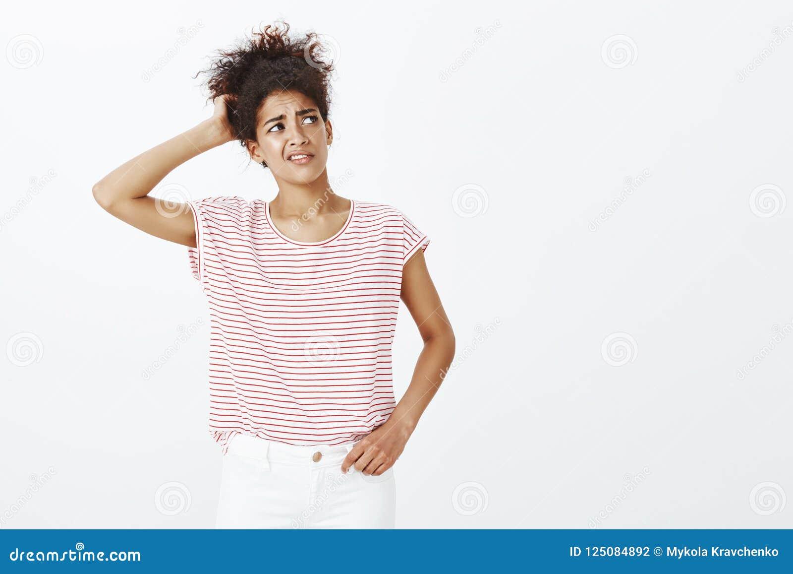 Salowy strzał niepewna atrakcyjna z włosami kobieta w pasiastej koszulce, chrobotliwym plecy, głowa i marszczyć brwi podczas gdy