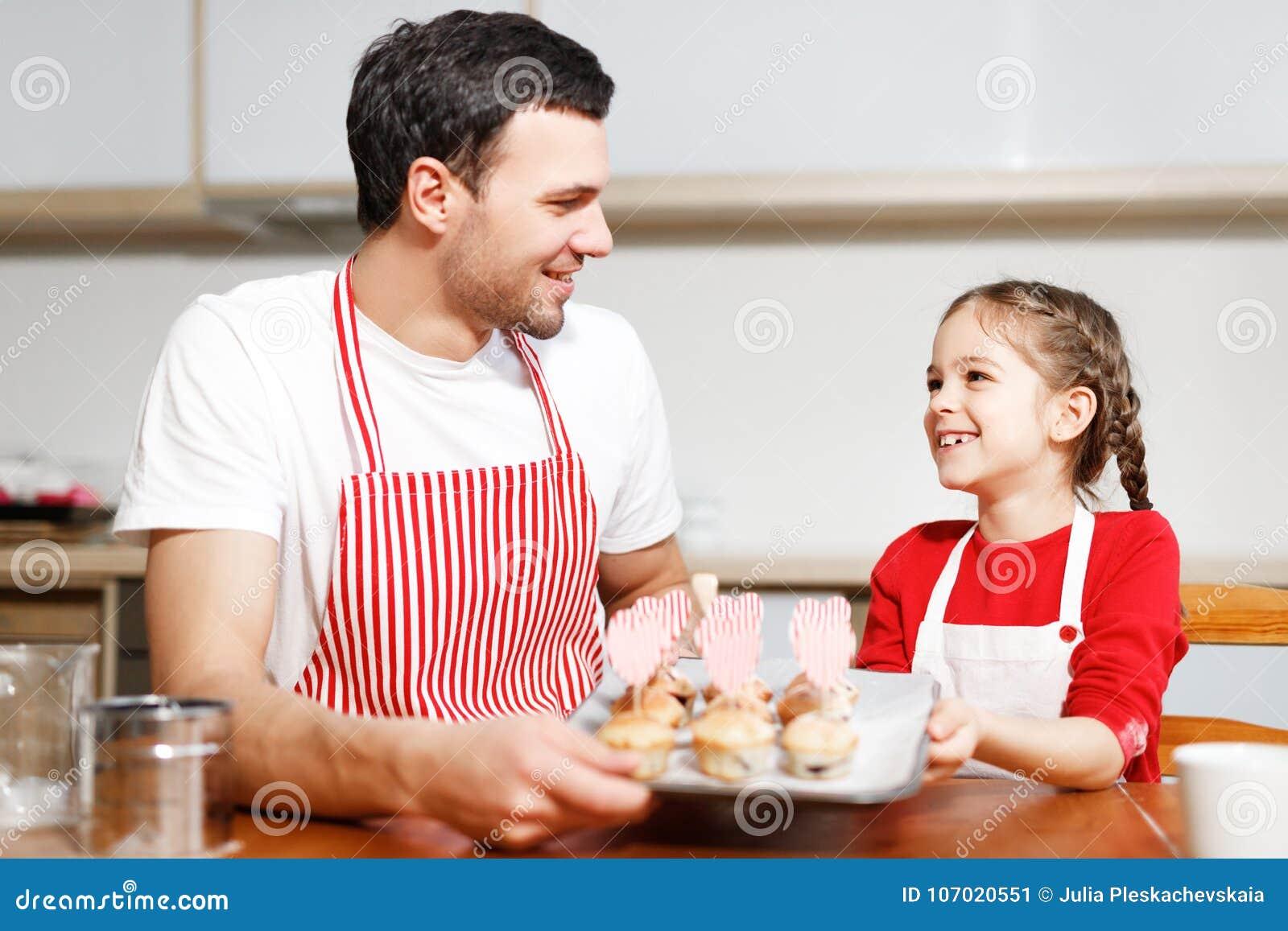 Salowy strzał przystojny mężczyzna jest ubranym pasiastego fartucha i jego małego ładnego żeńskiego dzieciaka chwyta ręcznie robi