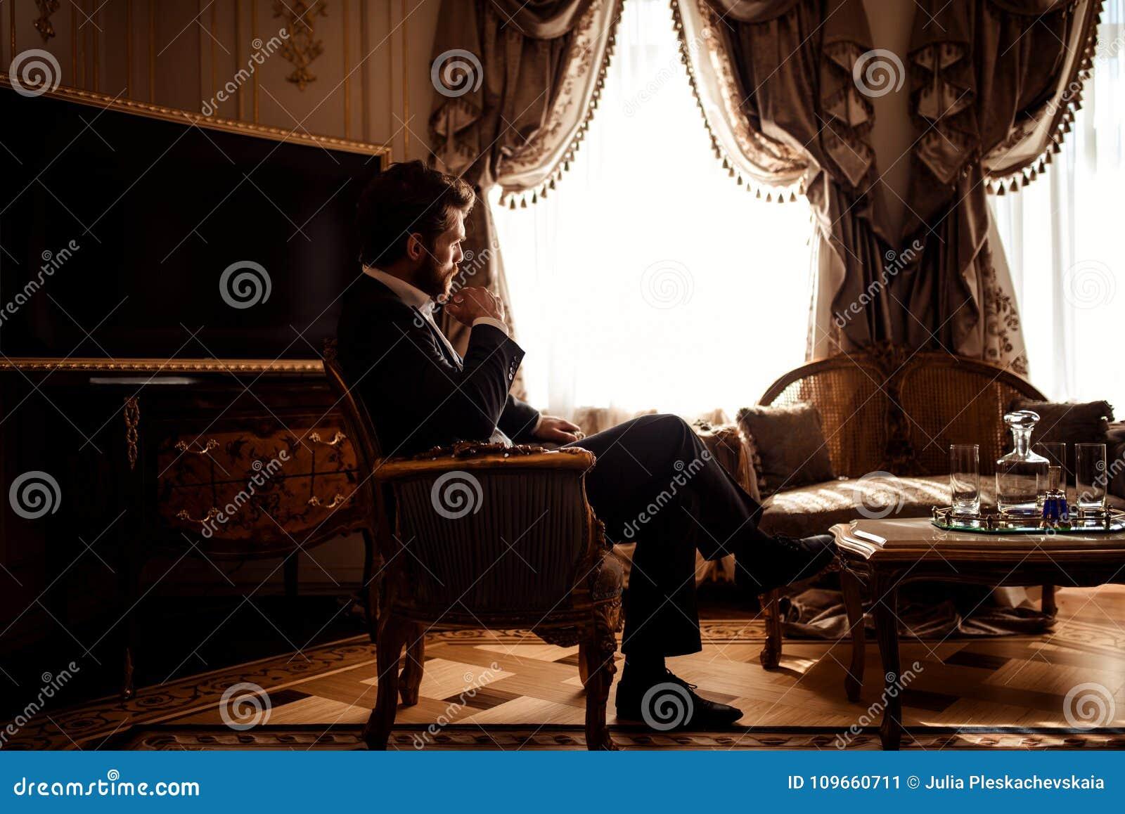 Salowy strzał rozważny wspaniały biznesmen lub przedsiębiorca jest ubranym czarnego kostium, siedzi w wygodnym pokoju z luksusowy
