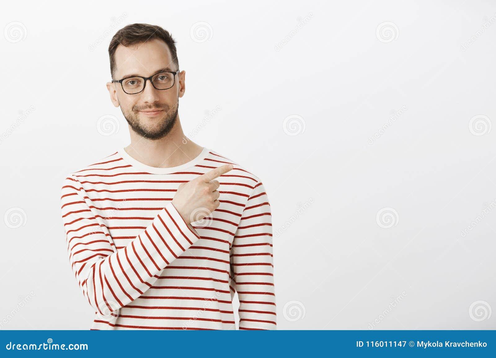 Salowy strzał smirking i wskazuje przy górnym prawym kątem ufny zadowolony europejski mężczyzna z szczecina w czarnym eyewear,