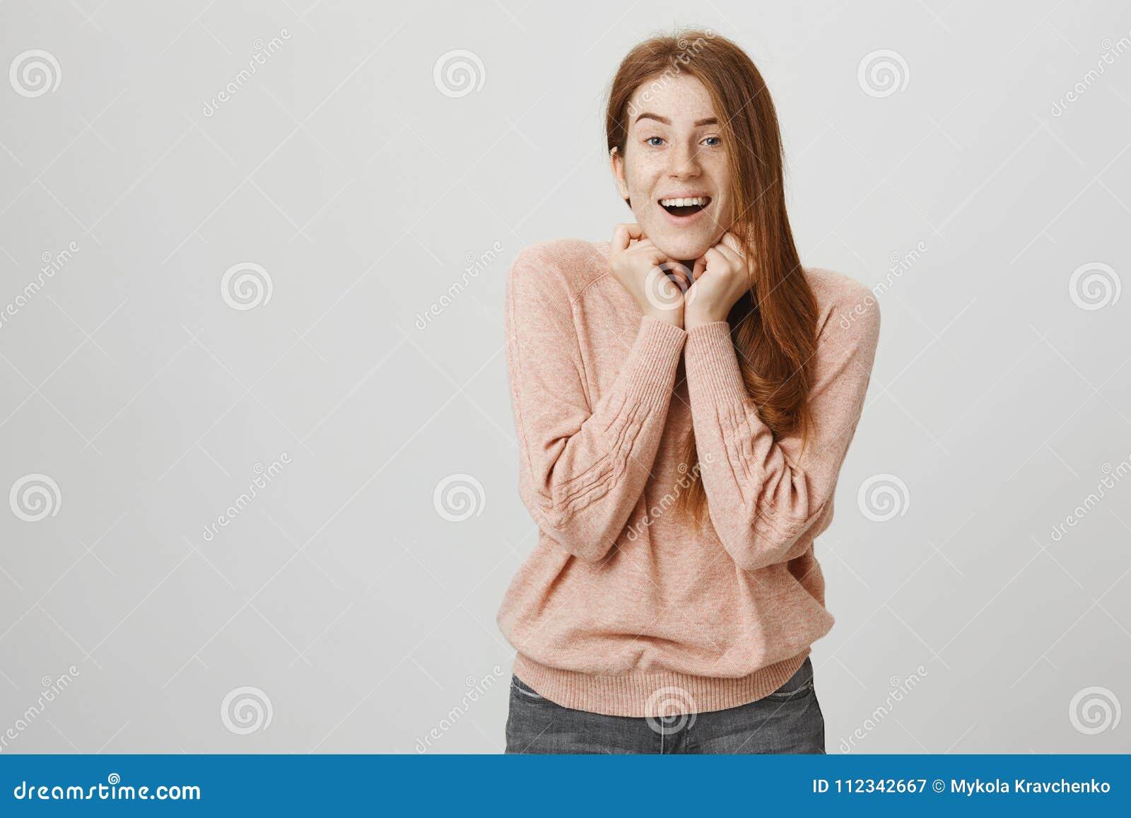 Salowy strzał uroczy i powabny rudzielec dziewczyny mienie wręcza blisko podbródka dotyka ślicznym szczeniakiem i pozycją