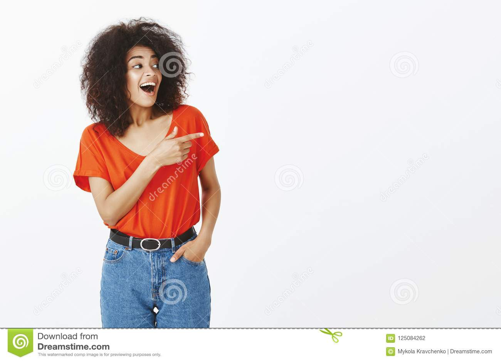 Salowy strzał zadziwiająca szczęśliwa otwarta kobieta z ciemną skórą, kędzierzawym włosy i,
