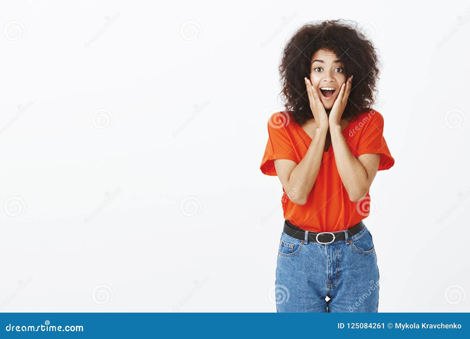 Salowy strzał zdziwiona zadowolona szczęśliwa ciemnoskóra kobieta z afro ostrzyżeniem, krzyczący od satysfakci i zdumienia