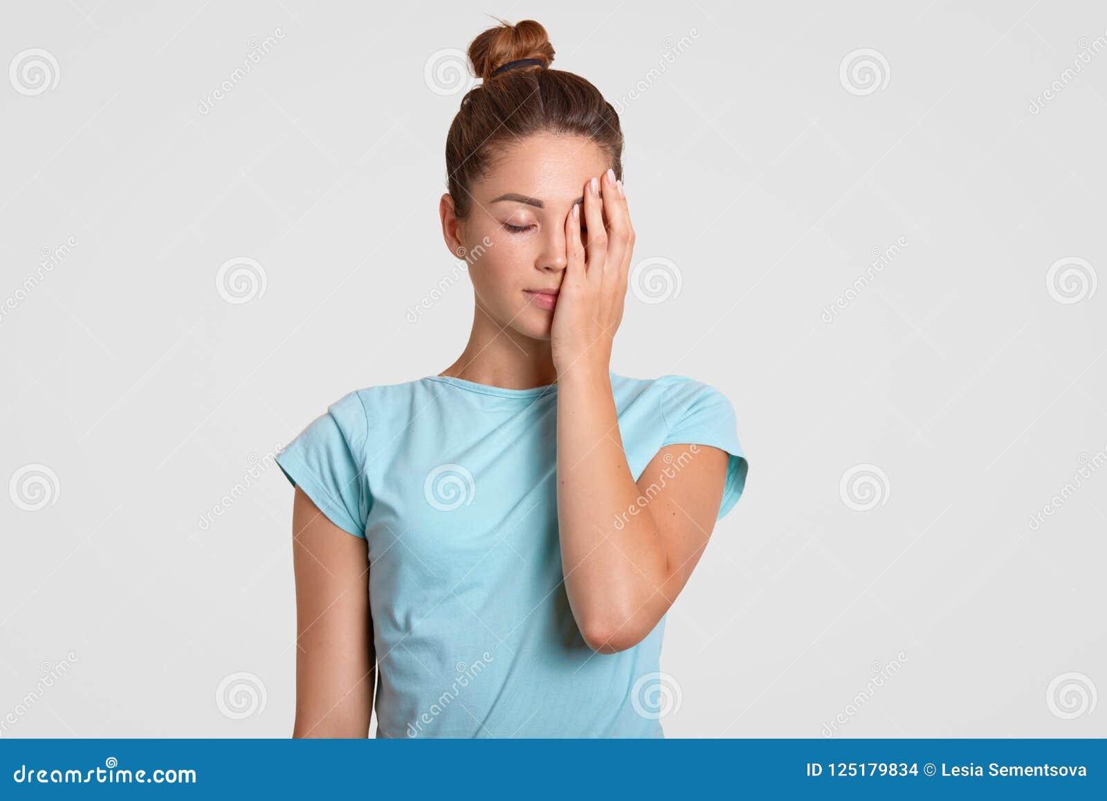 Salowy strzał zmęczona sportsmenka koncentrował pokrywy stawiają czoło z ręką, ubierającą w przypadkowej t koszula, utrzymań oczy