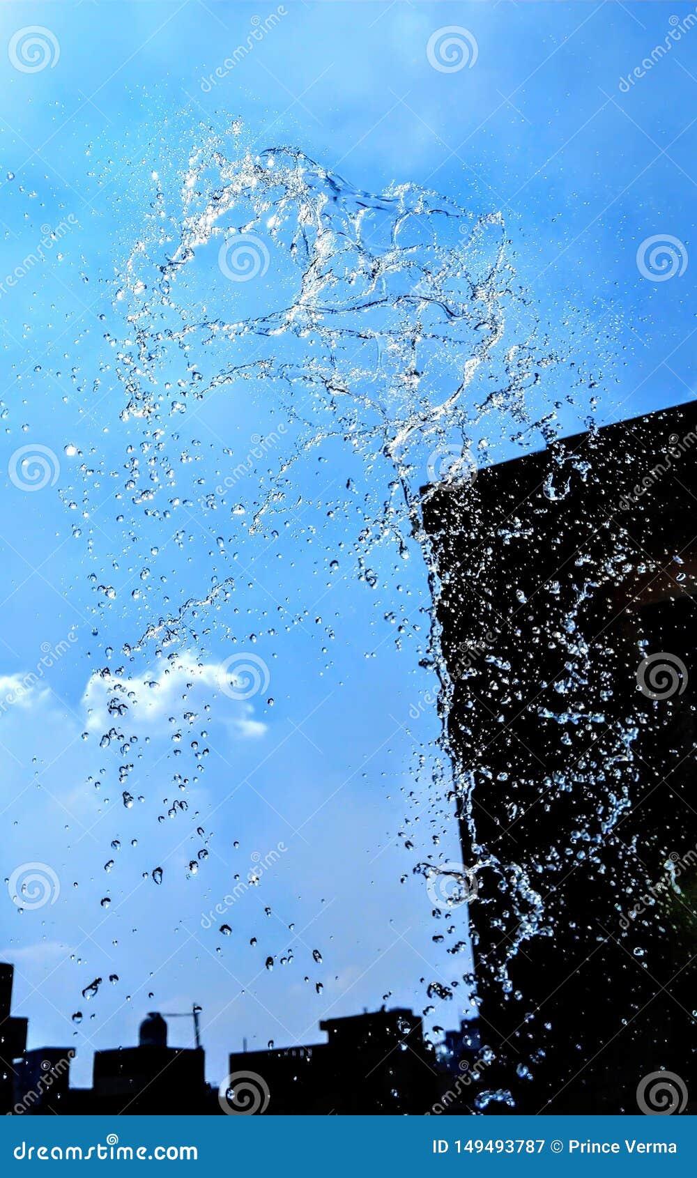 Salpicando el agua aislada en fondo azul