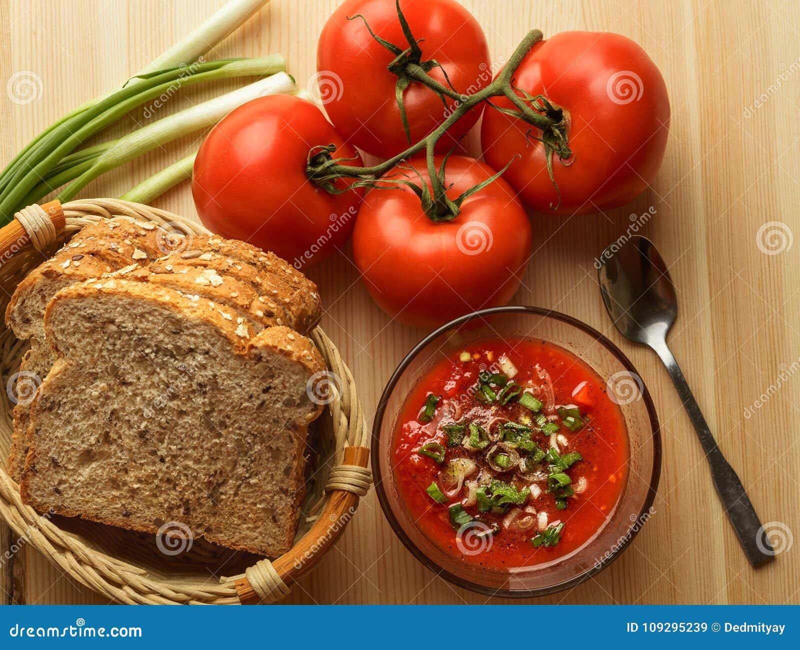 Salsa de tomate en el bol de vidrio, pan fresco, cebolla en la tabla de madera, ingredientes de la salsa para la comida vegetaria