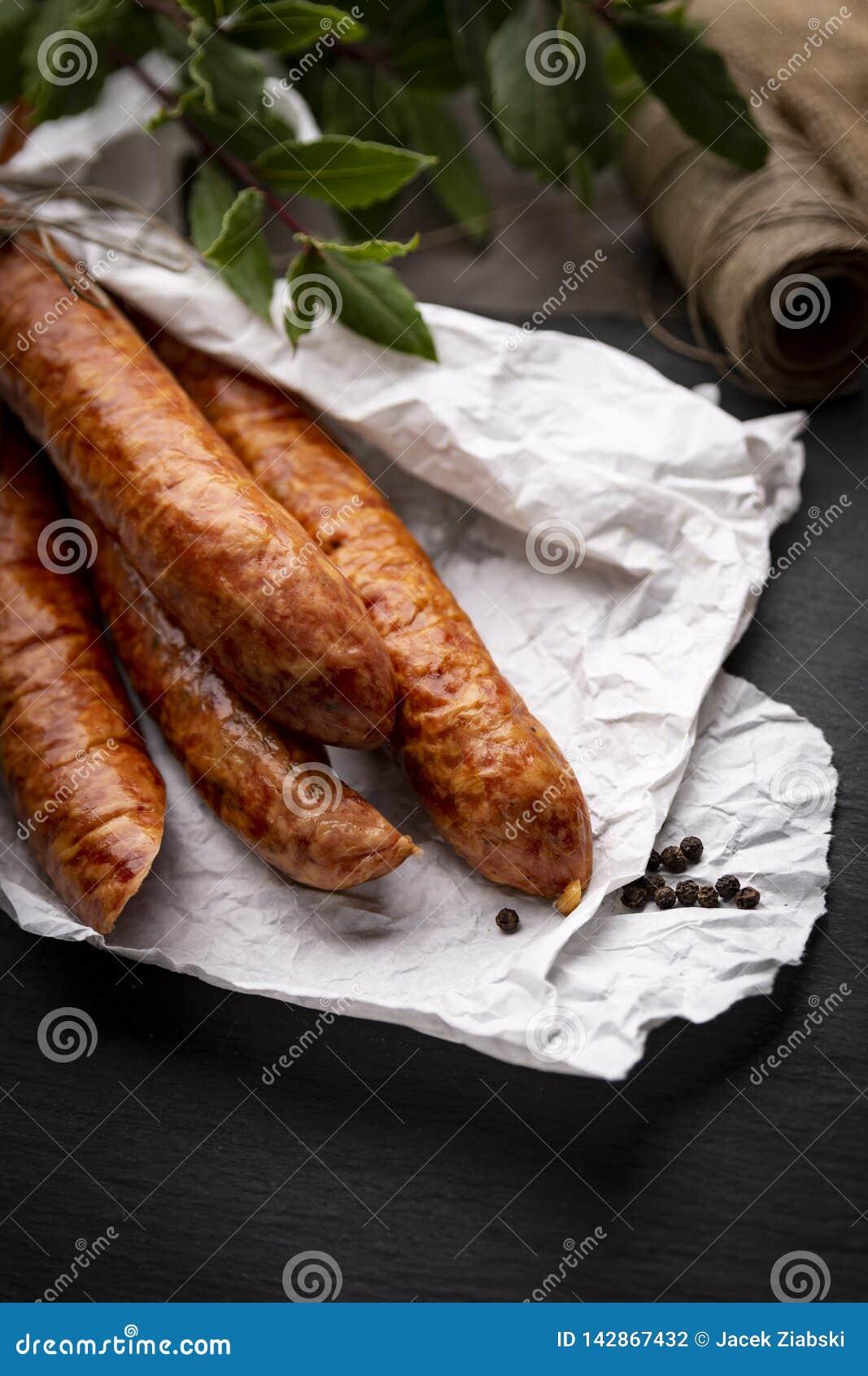 Salsiccia affumicata in carta su un piano di lavoro scuro della cucina